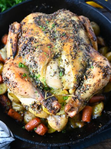 A whole lemon garlic roasted chicken on top of roasted veggies in a cast iron skillet.