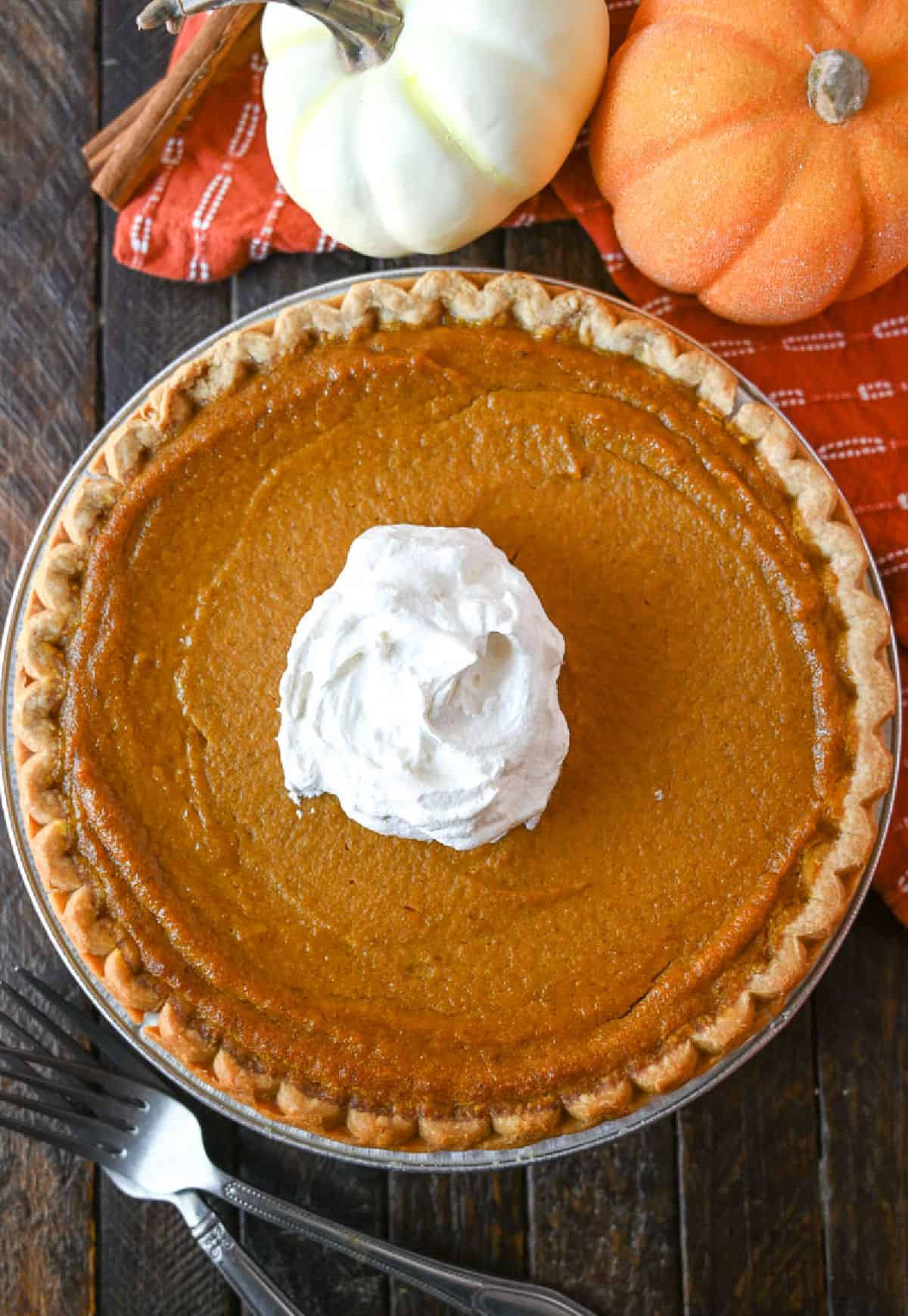 A whole buttermilk pumpkin pie with whipped cream in the center.