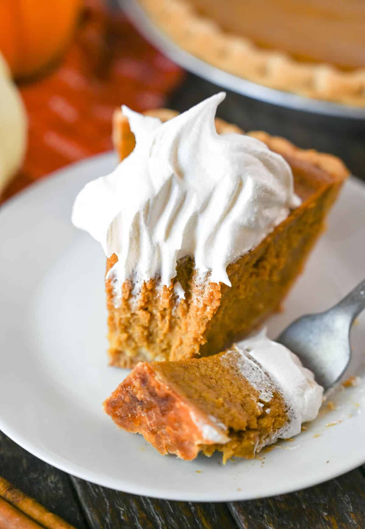 A bite of pumpkin pie on a fork laying next to a piece of pie.