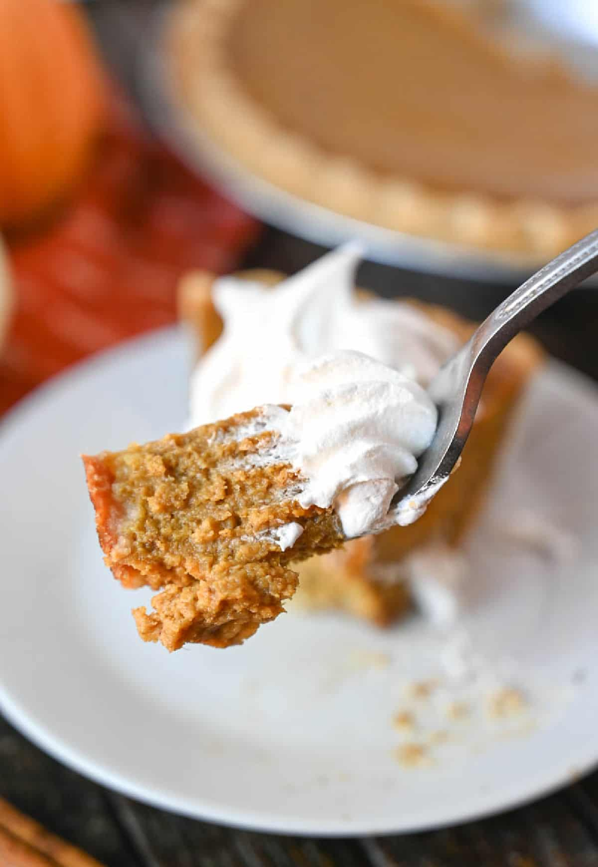 A bite of pumpkin pir with whipped cream on a fork.