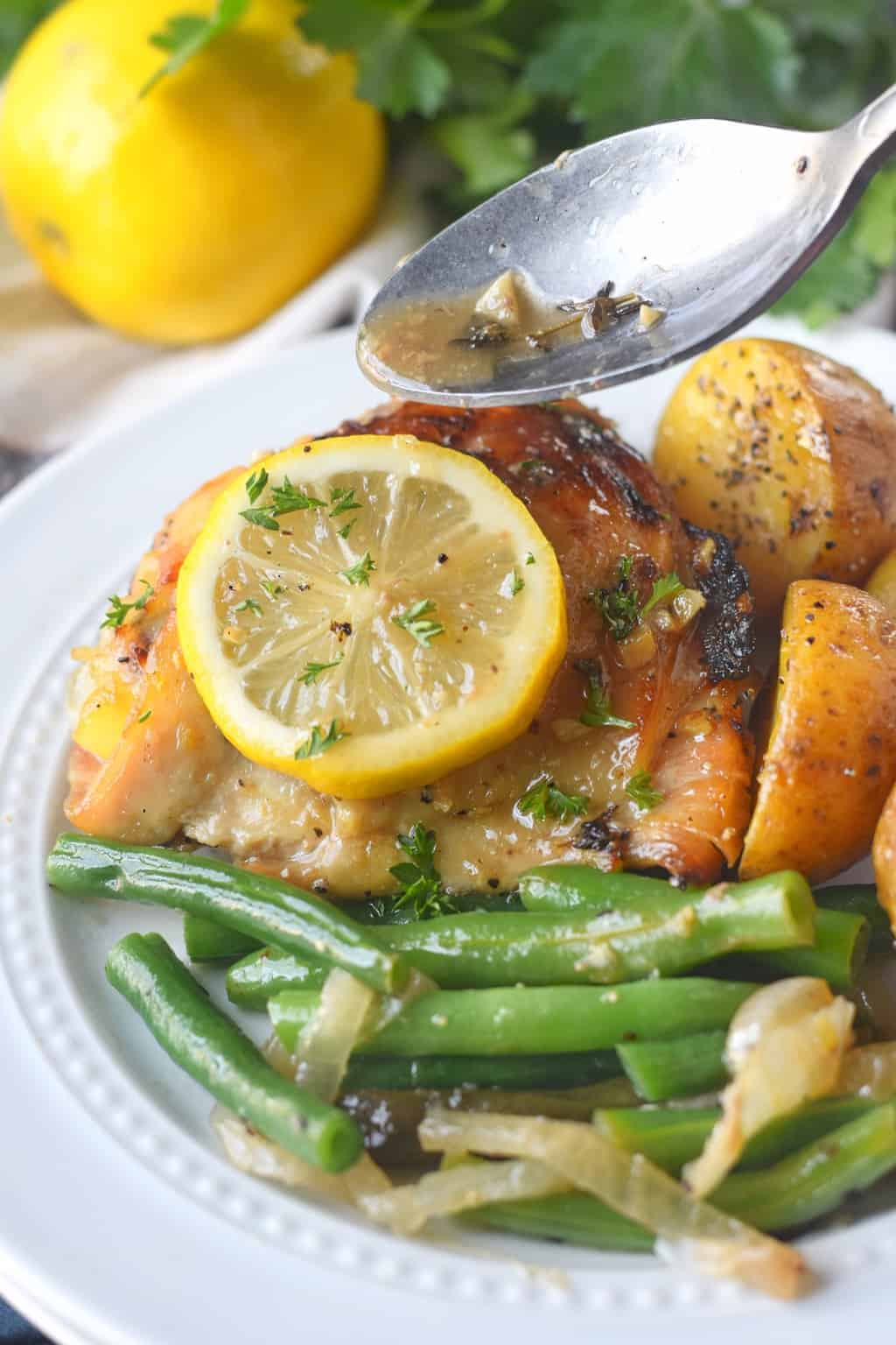 Chicken thigh with a side of potatoes and green beans on a white plate.