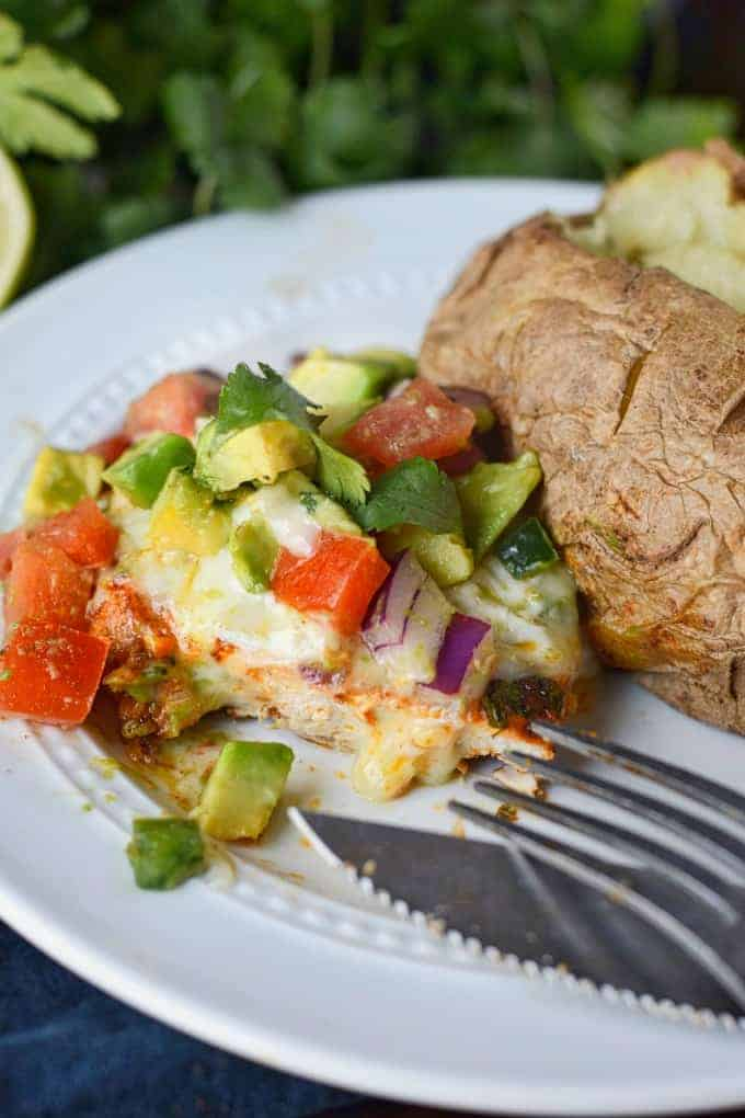 Grilled chicken on a white plate with avocado salsa on top and a baked potato on the side.
