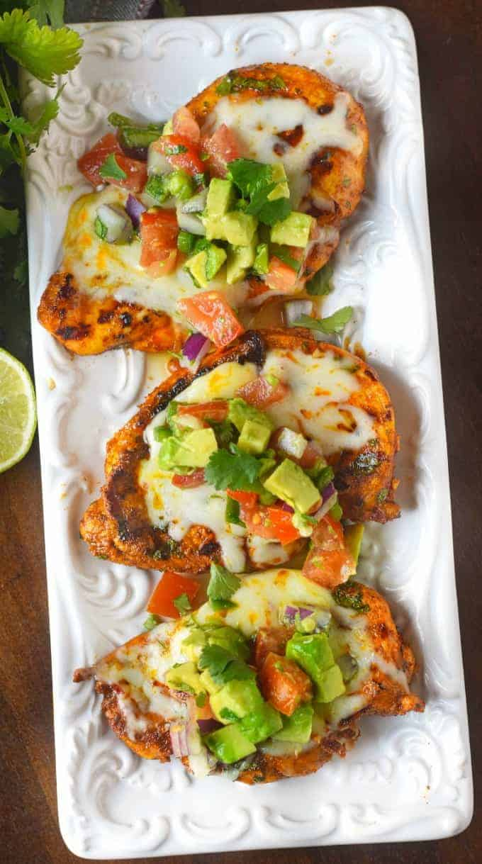 Three grilled chicken breasts on a whilt platter with avocado salsa on top of each one.