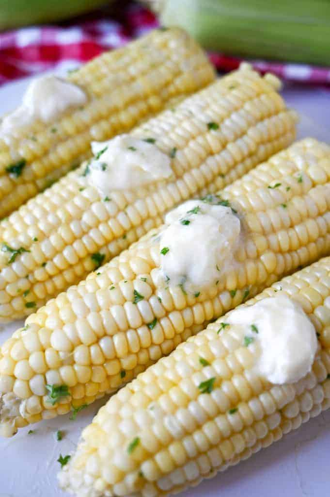 Microwave corn on the cob on a white plate with dabs of butter on each one.