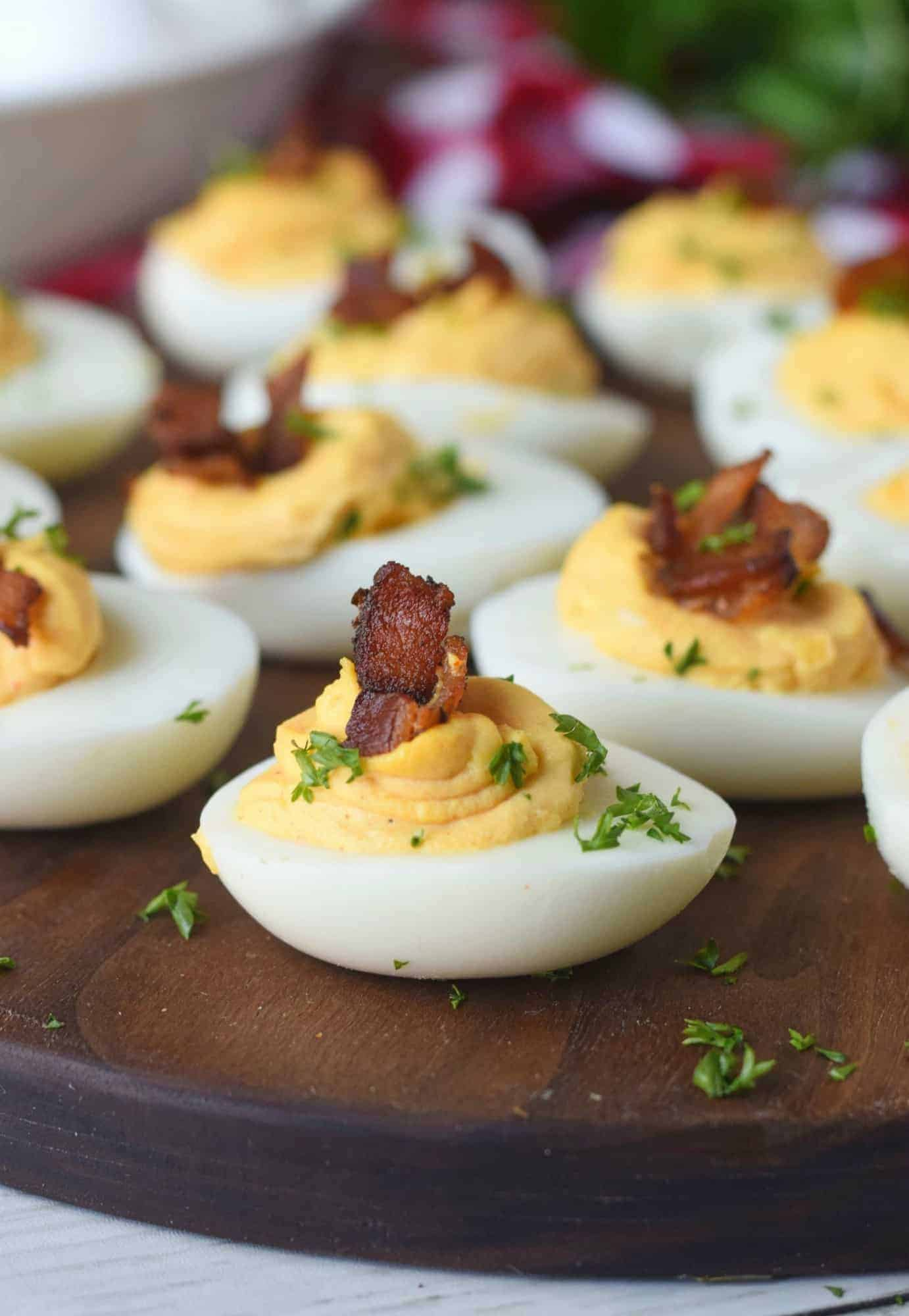Chipotle bacon deviled eggs on a small cutting board. With parsley sprinkled on top.
