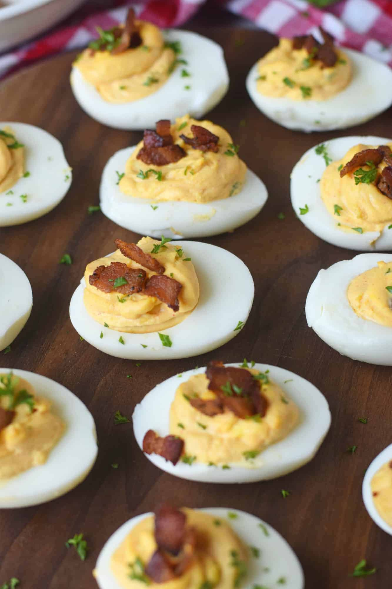 Twelve chipotle bacon deviled eggs on a serving board with a red checkered napkin .