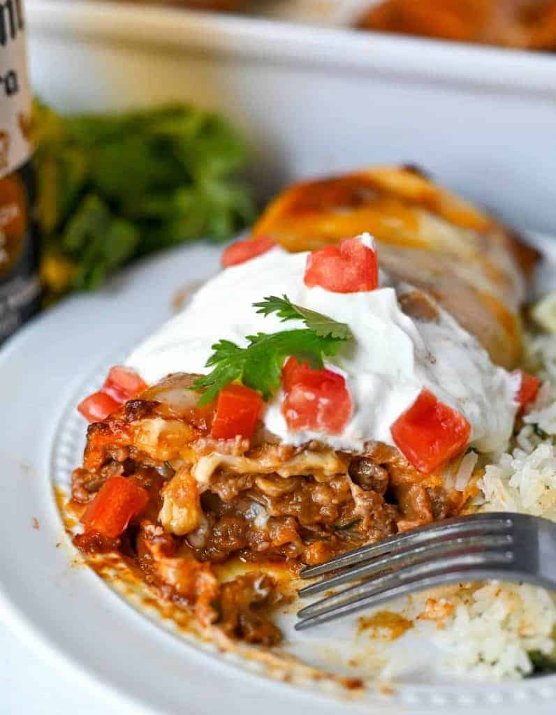 beef burrito on a white plate with sourcream on top and diced tomatoes. the end cut off and gooey, cheesy beef is oozing out.