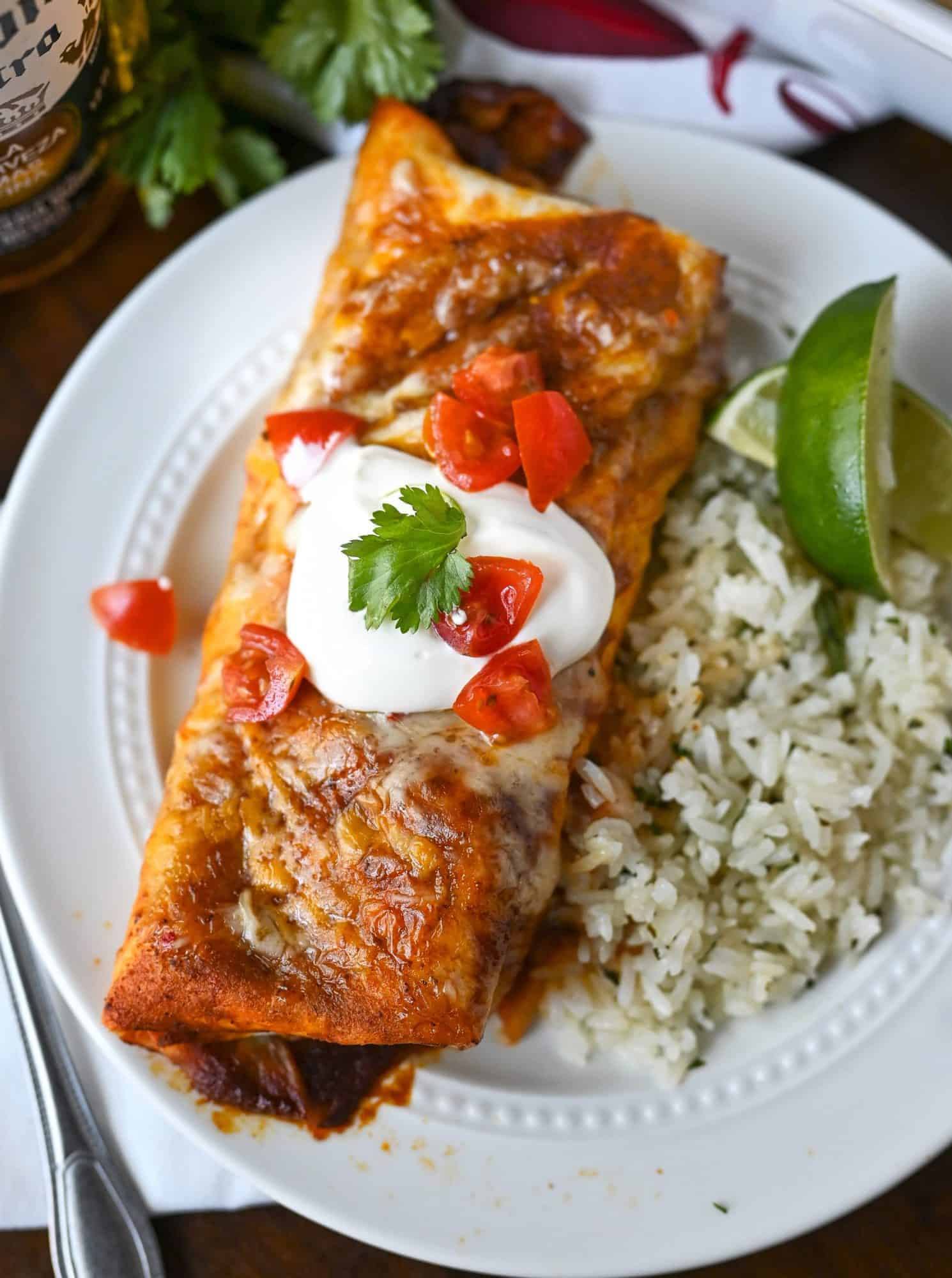 Beef burrito on a white plate, with sourcream and diced tomatoes on top. With a side of cilantro rice and slices of limes.