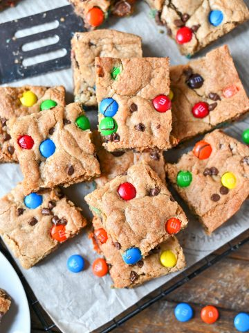 M&M cookie bars all cut and piled on top of each other.