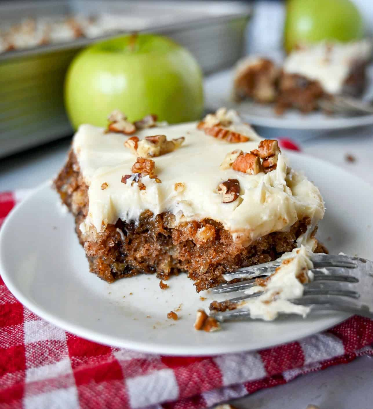 Apple cake with cream cheese frosting and pecans on top of a wgite plate and a fork on the side.