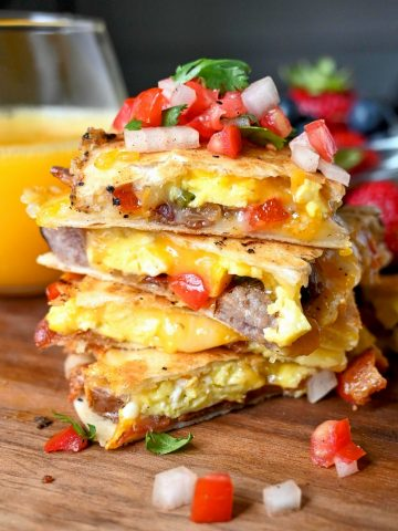 Breakfast quesadilla cut into fourths and stacked on top of each other with a pile of pico de gallo on top.