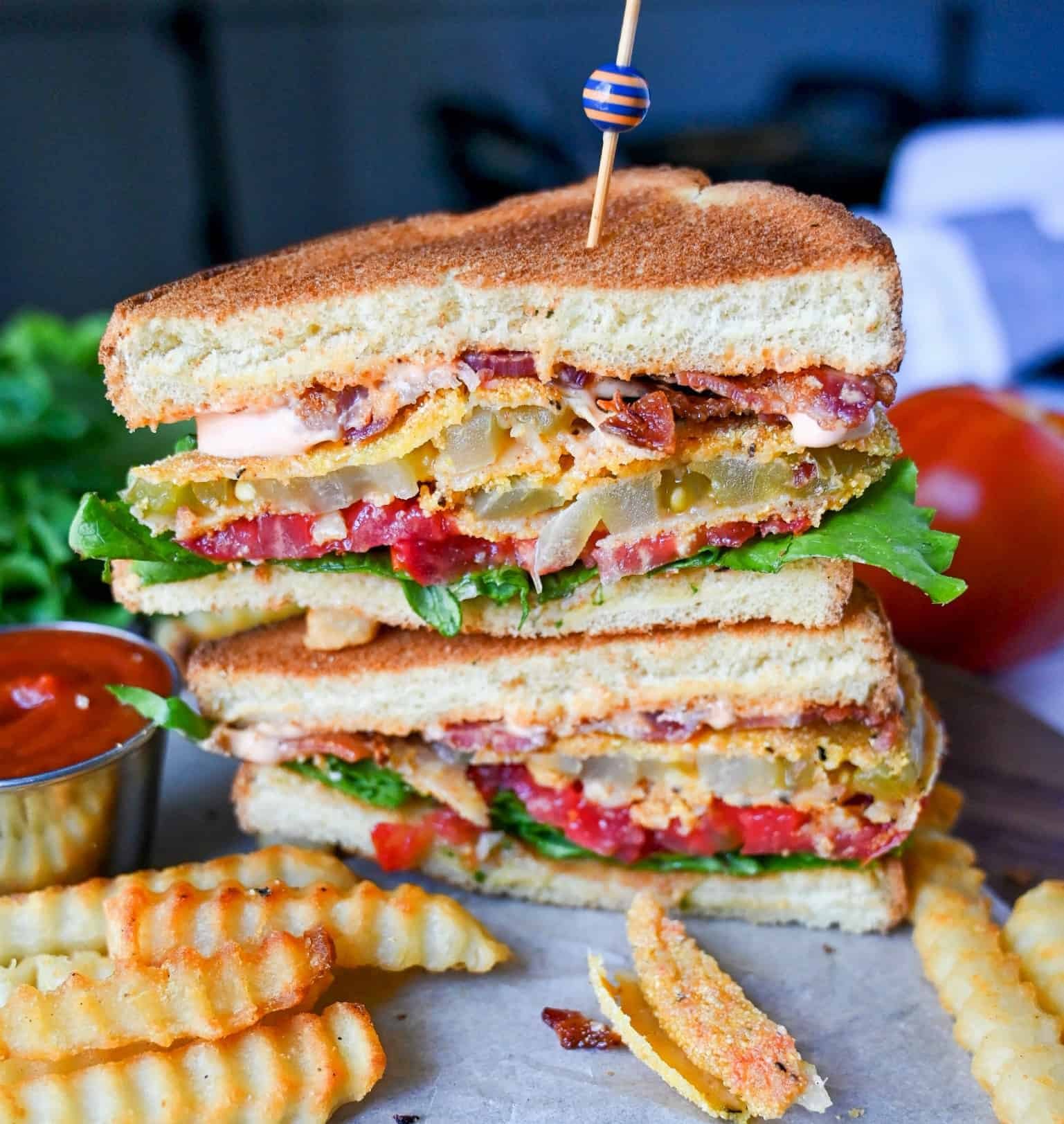 Fried green tomato sandwich cut in half and stacked on top of each other. With french fries and ketchup on the side.