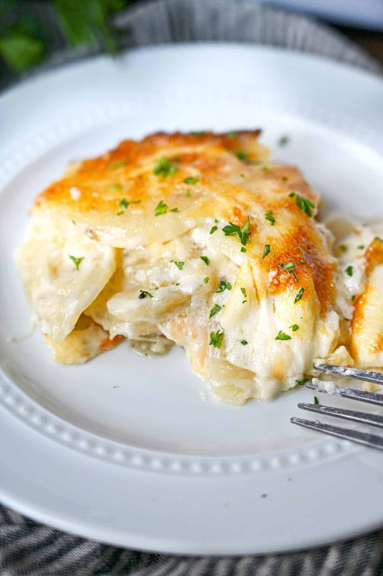 A scoop of potatoes au gratin on a small white plate with a fork.