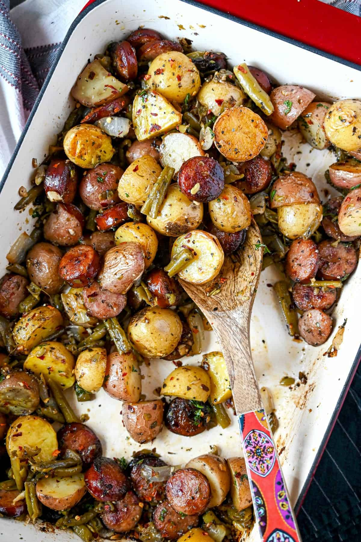 Sausage, green beans and potatoes all in a casserole dish with a wooden spoon.
