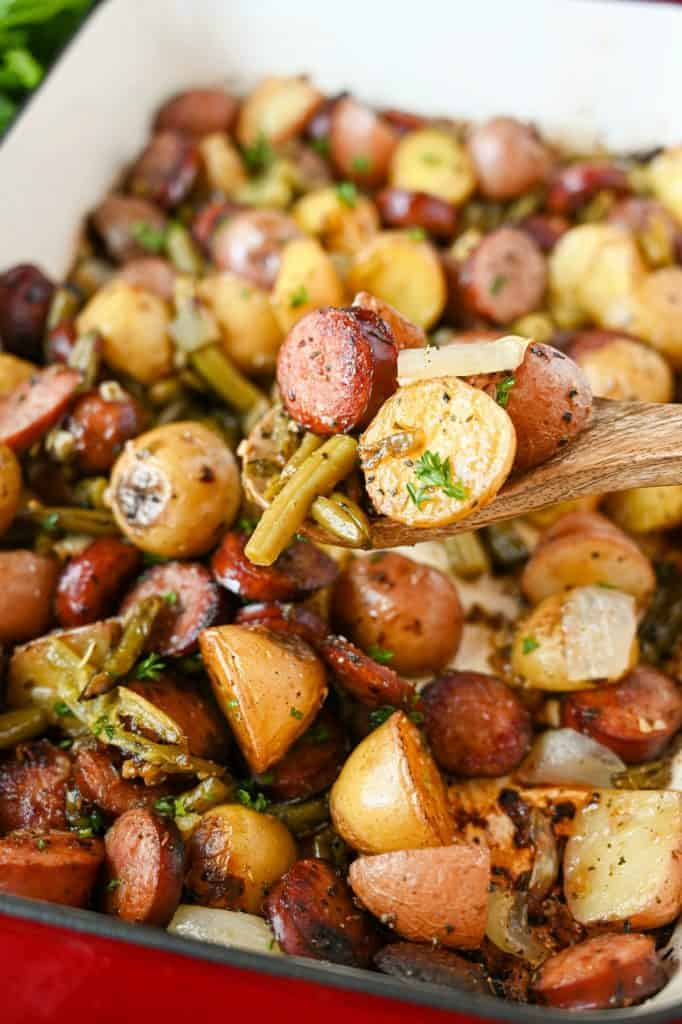 A wooden spoon scooping out some sausage, green beans and potato bake out of a casserole dish.