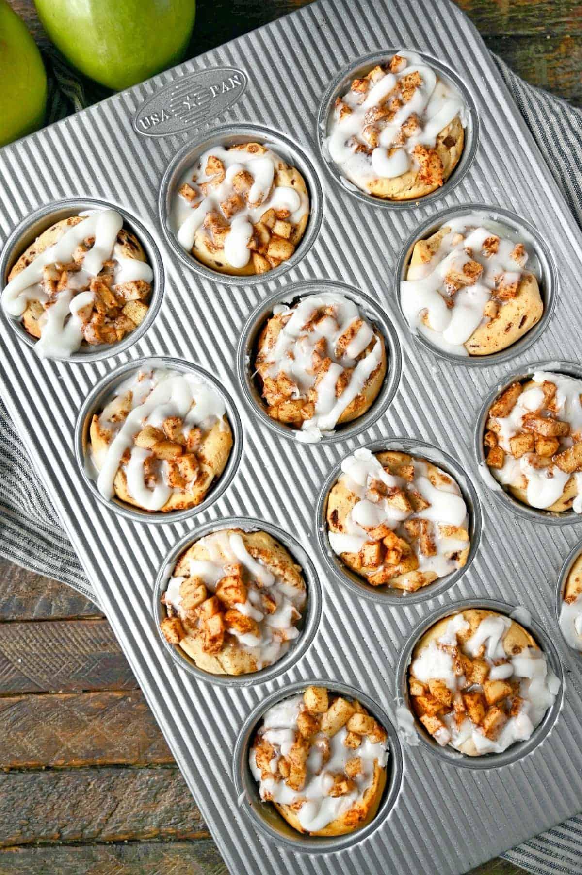 Apple pie cinnamon rolls in a 12 cup muffin tin.