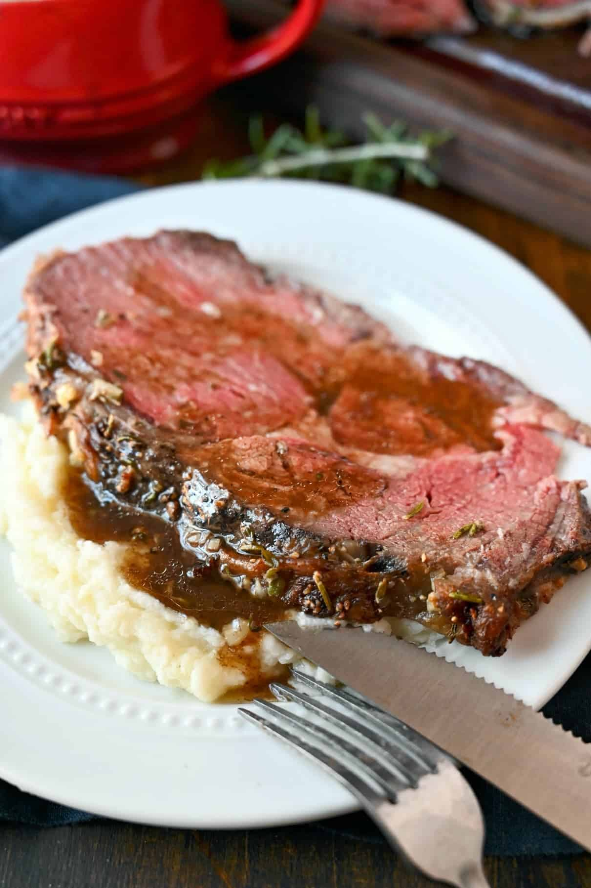 Rib eye roast slice on a white plate with mashed potatoes and gravy on top.