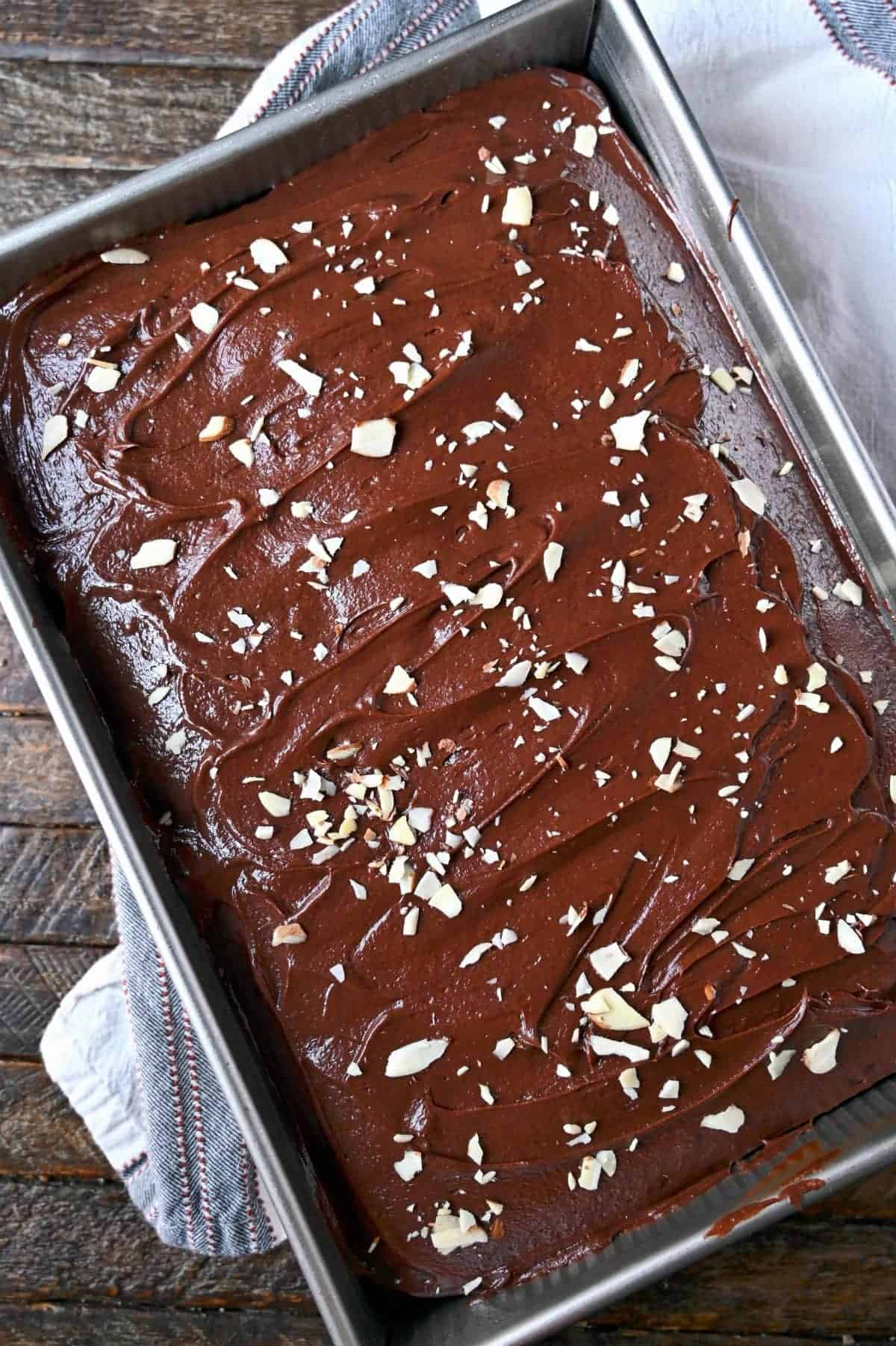 Chocolate mayonnaise cake in a 9x13 baking pan with chocolate frosting and slivered almonds on top.