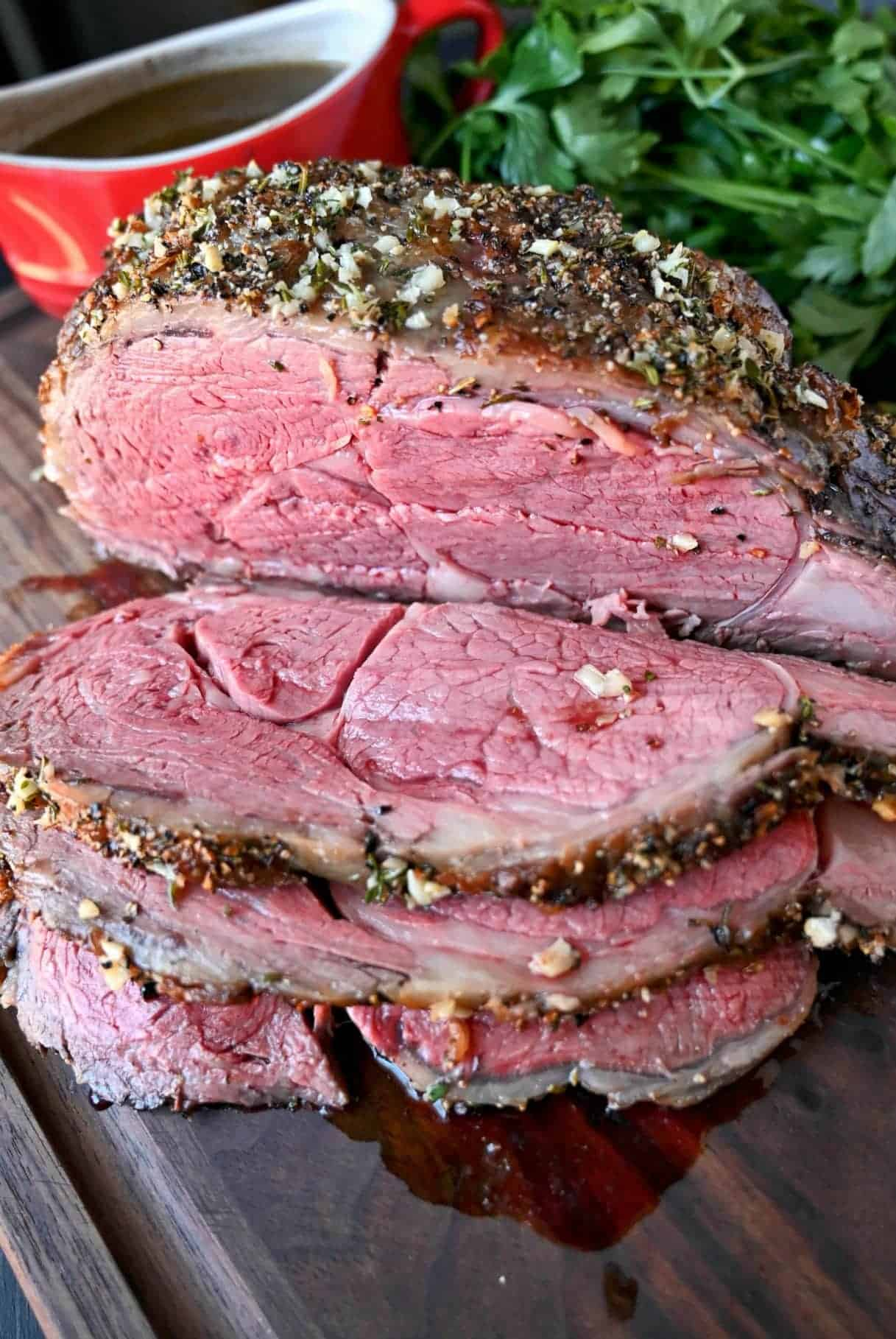 Herb crusted rib eye roast with three thin slices cut out of it.