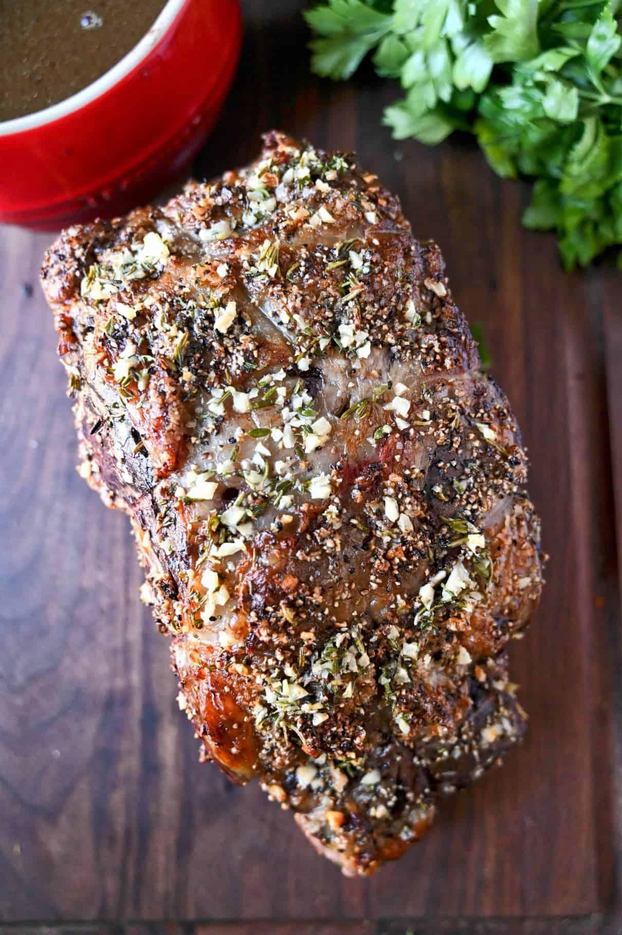 Herb crusted rib eye roast on a cutting board ready to be sliced.