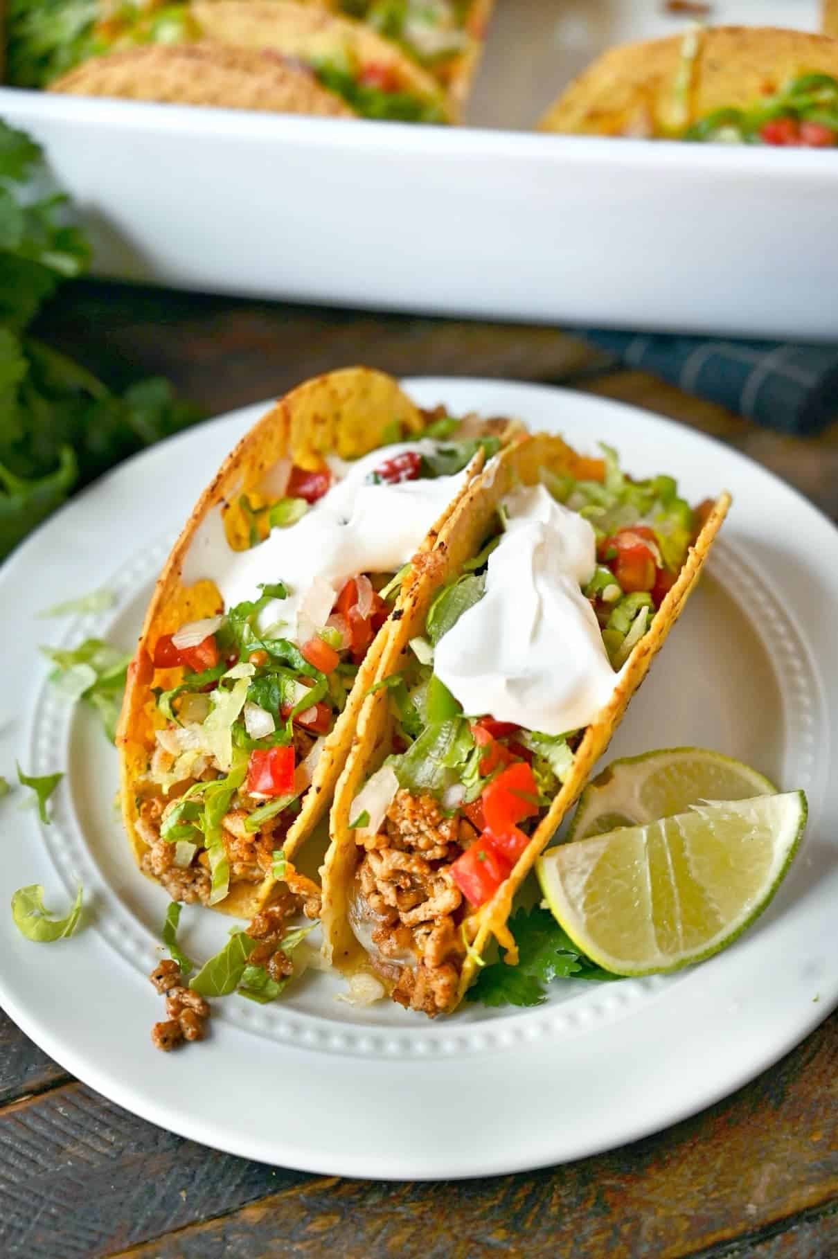 Two baked chicken tacos on a white plate with two lime slices.