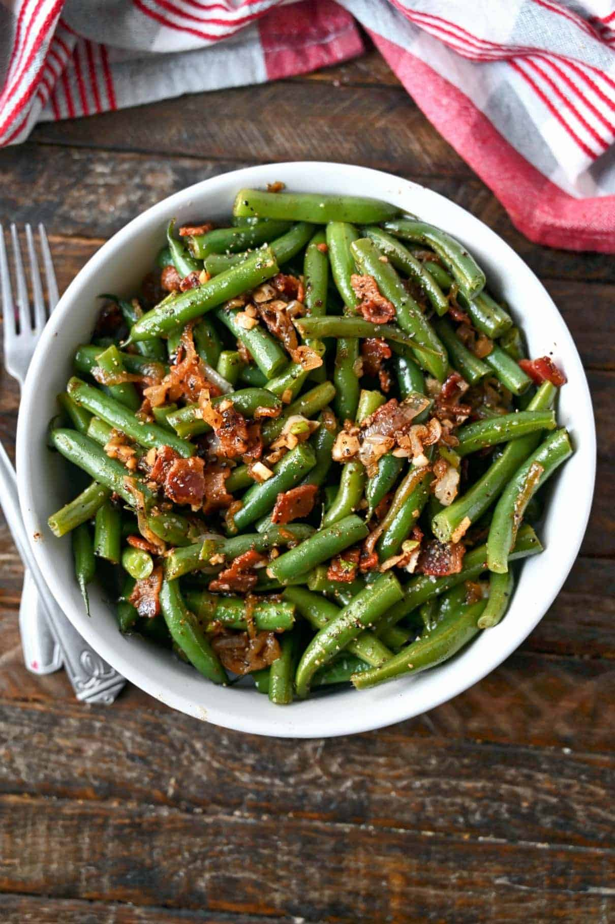 Green beans with bacon and caramelized onion in a white bowl.