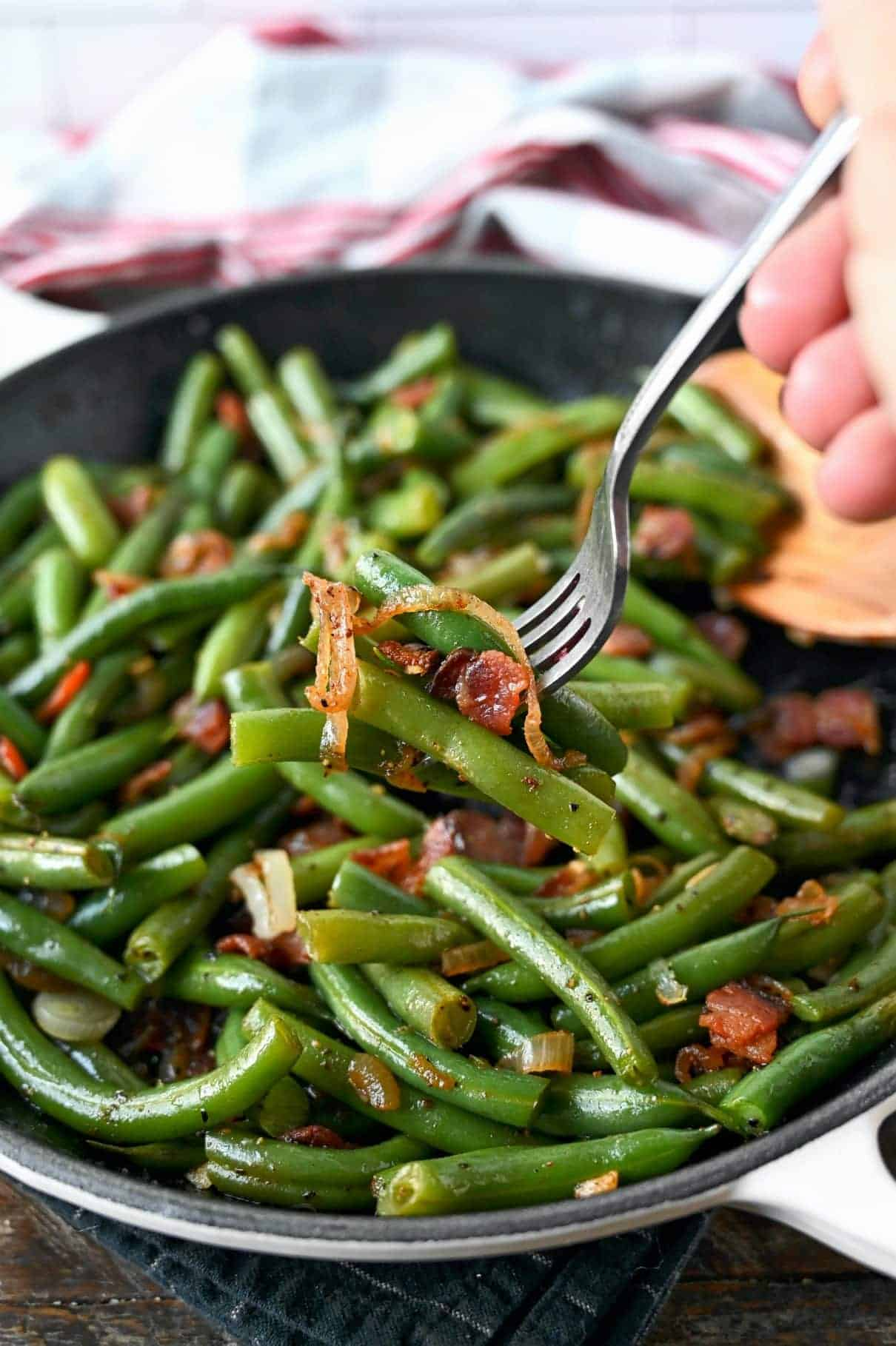 Green beans and bacon in a skillet with a fork picking up a bite.