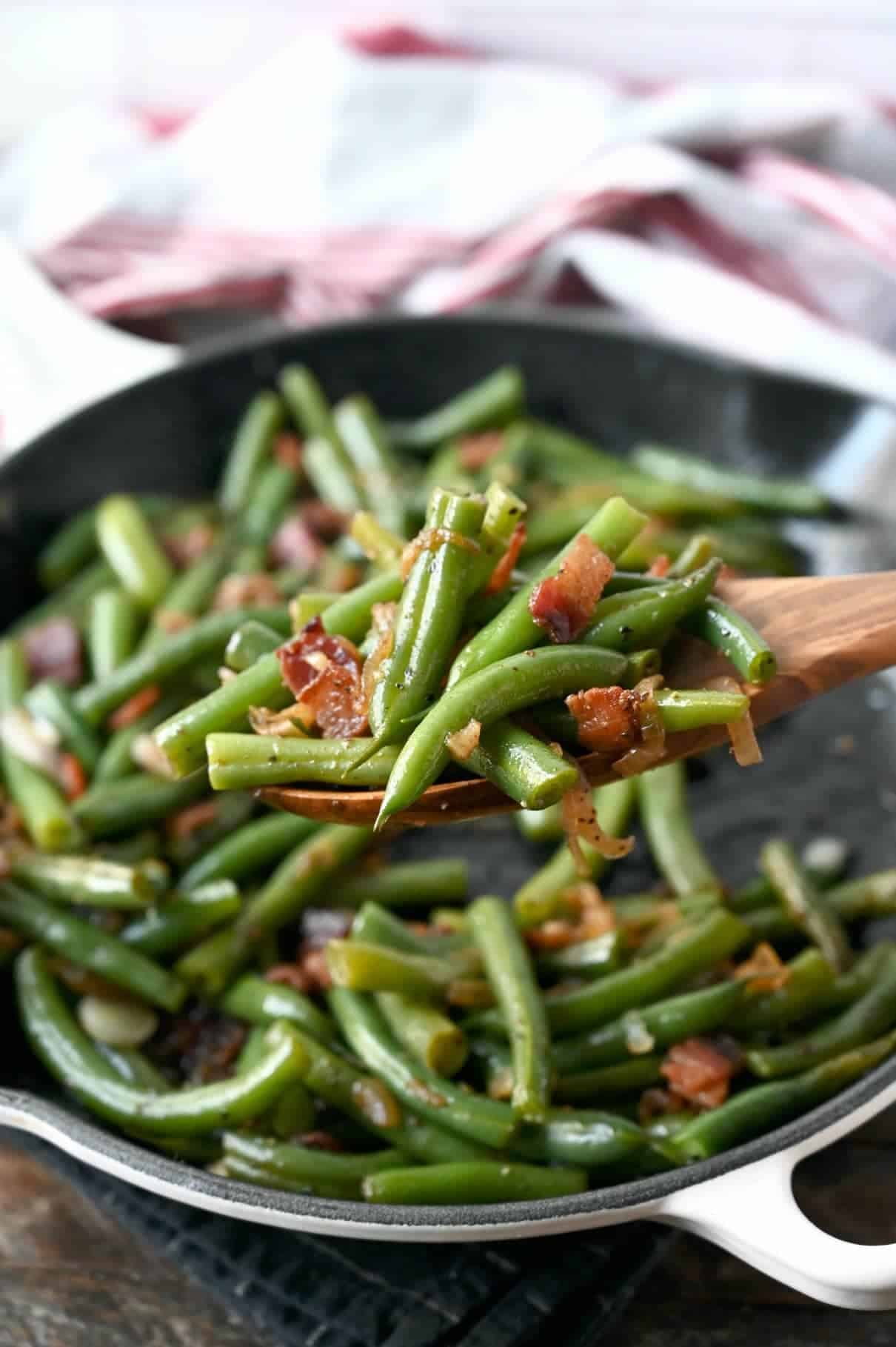 Green beans and bacon in a skillet with a wooden spoon picking up a scoop.