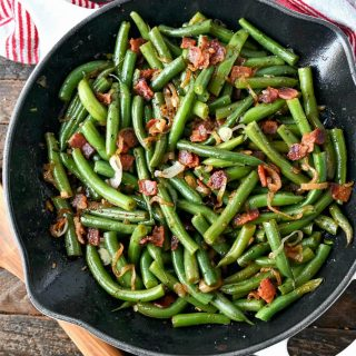 Green beans and bacon all in a skillet with a wooden spoon on the side.