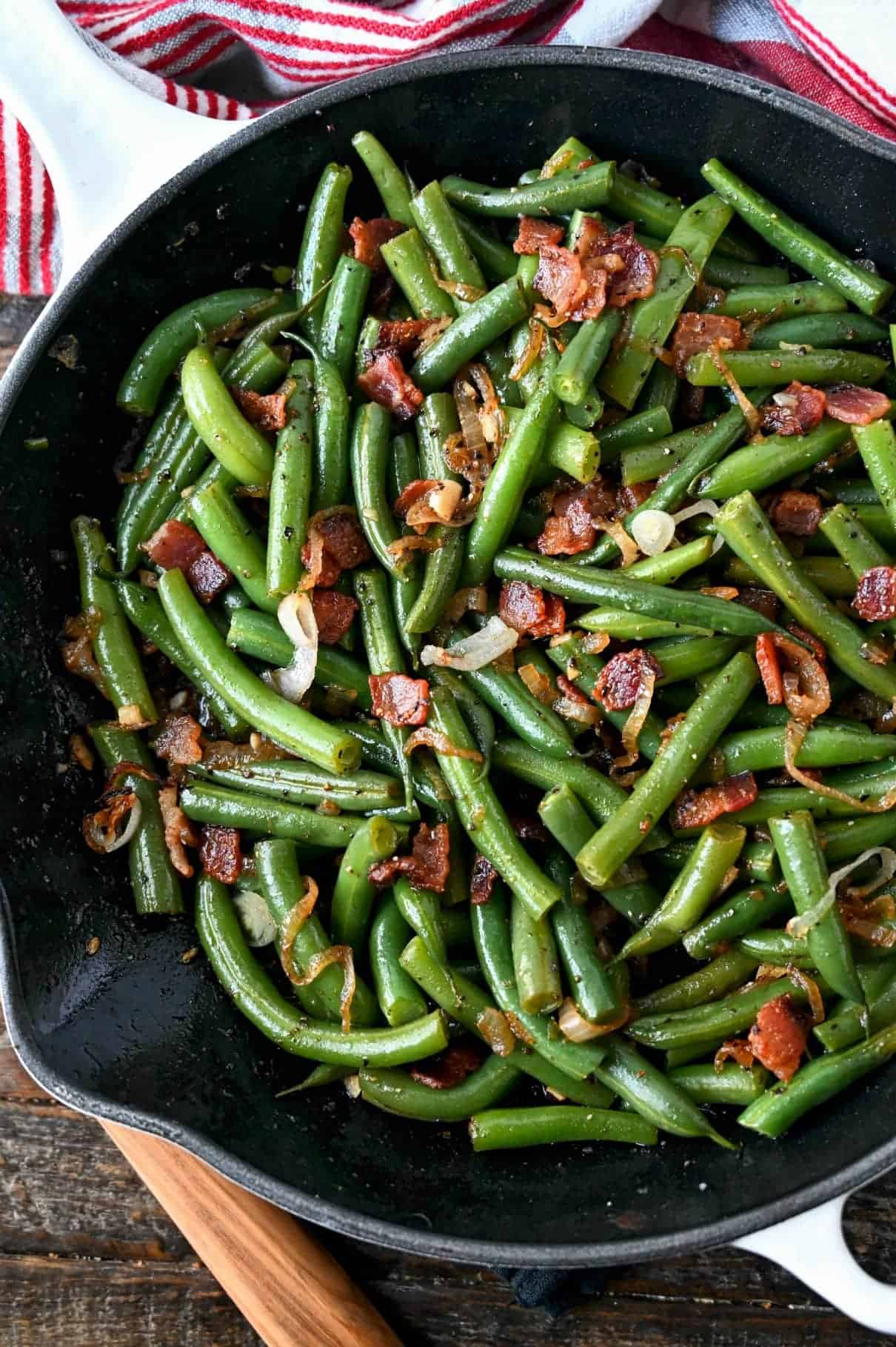 Close up photo of green beans and bacon in a skillet.