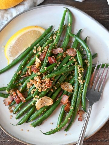 Green beans and bacon on a plate with a lemon slice and fork.