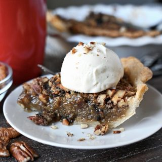 A slice of maple pecan pie with a scoop of vanille ice cream on top.