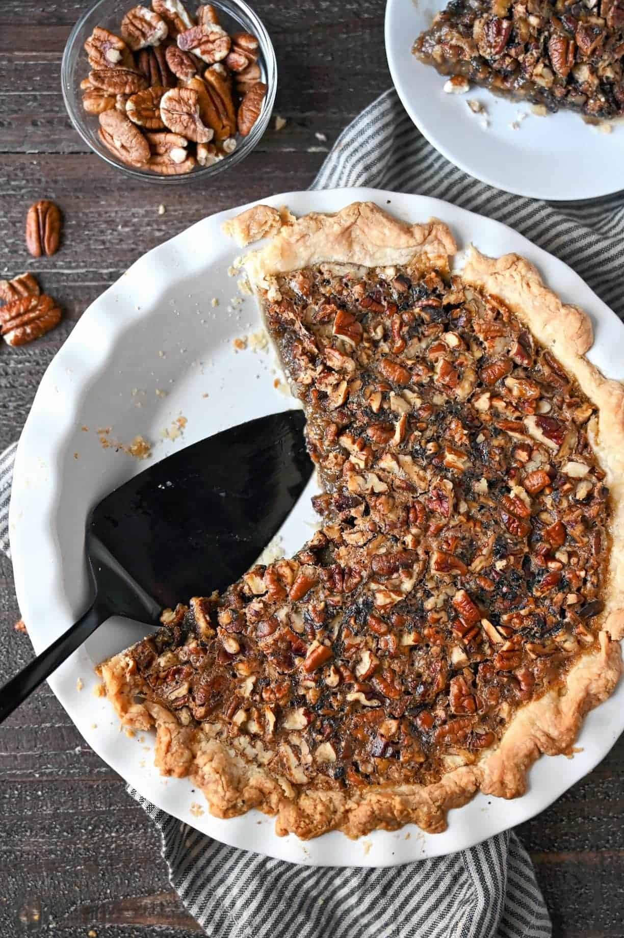 A maple pecan pie in a pie dish with two pieces removed.
