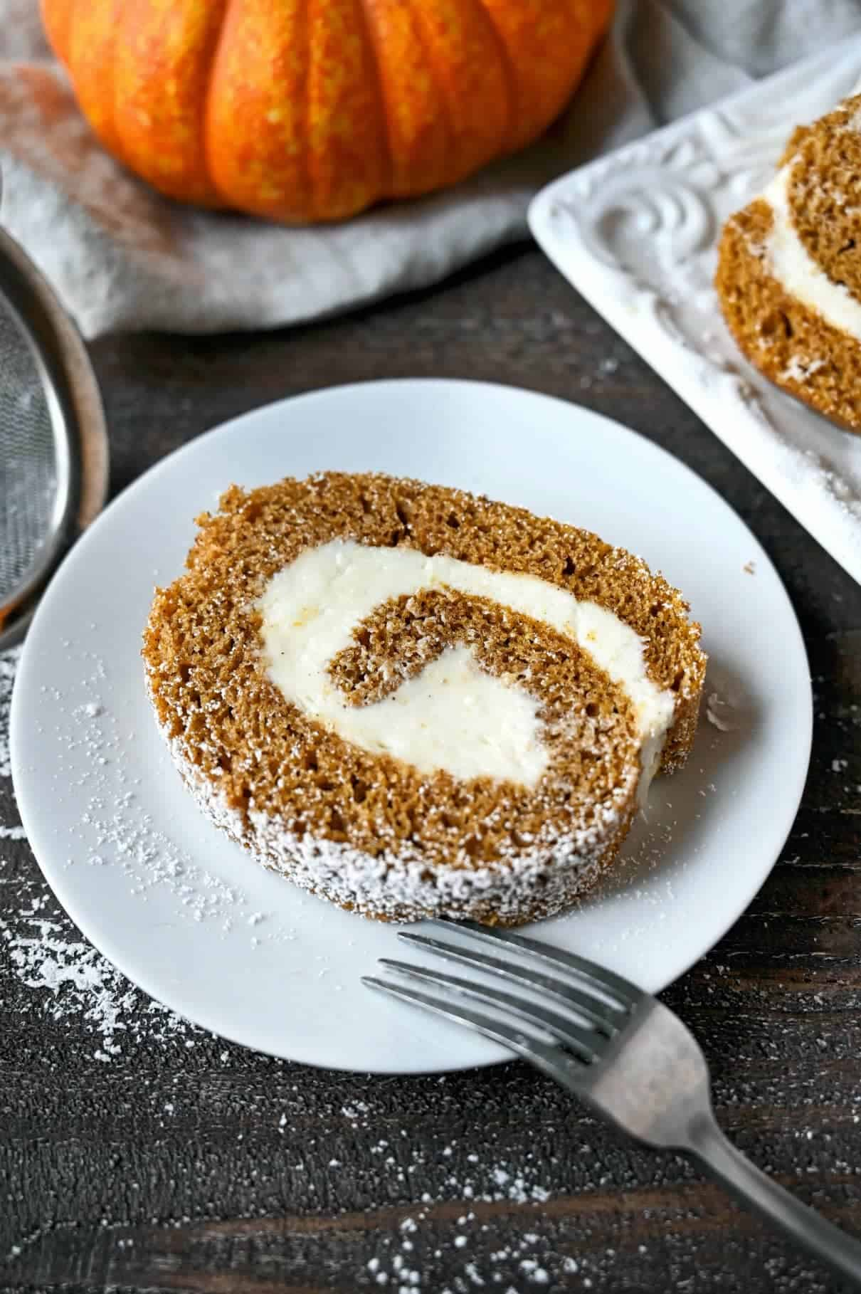 Pumpkin roll cake slice on a small white plate with a fork.