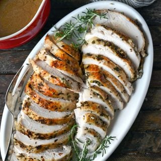Two turkey breats thinly sliced on a white platter with rosemary sprigs.
