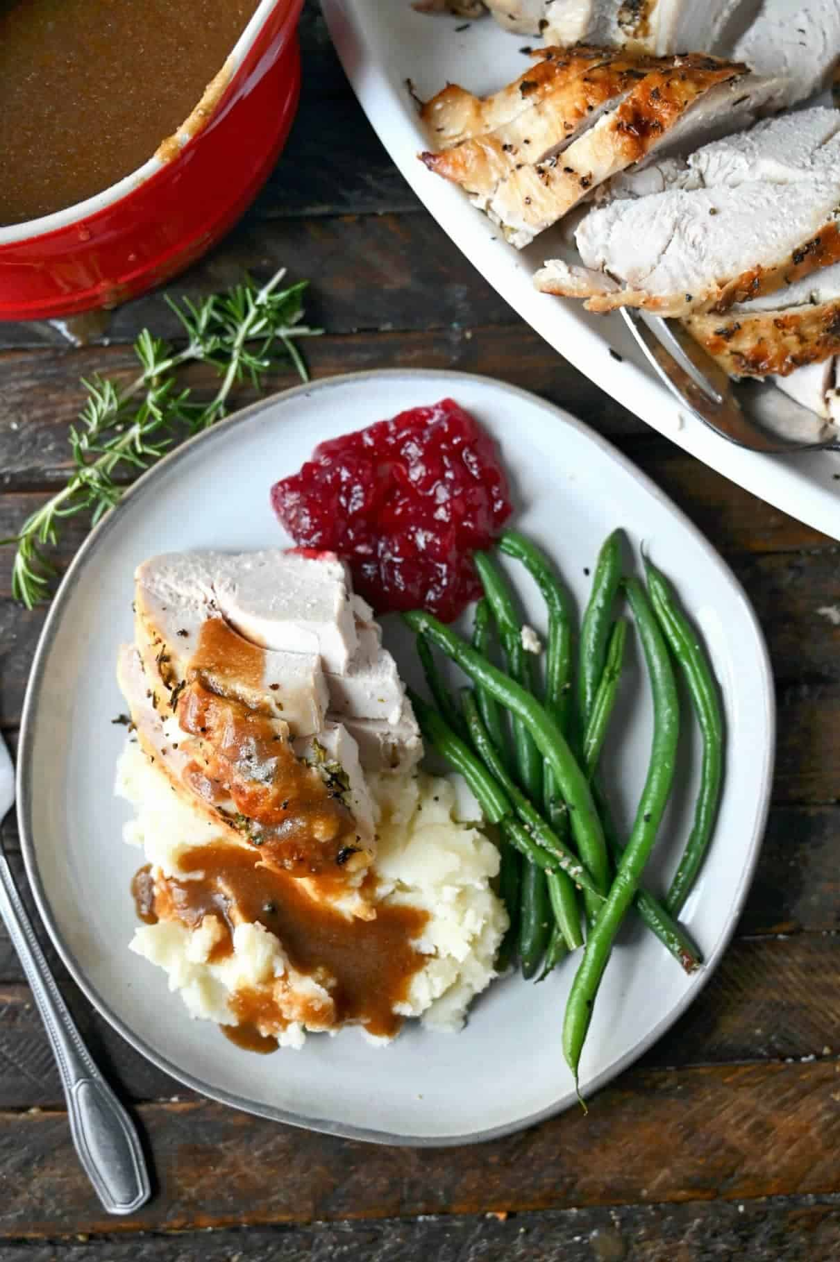 Turkey, mashed potatoes, green beans and cranberries on a white plate.