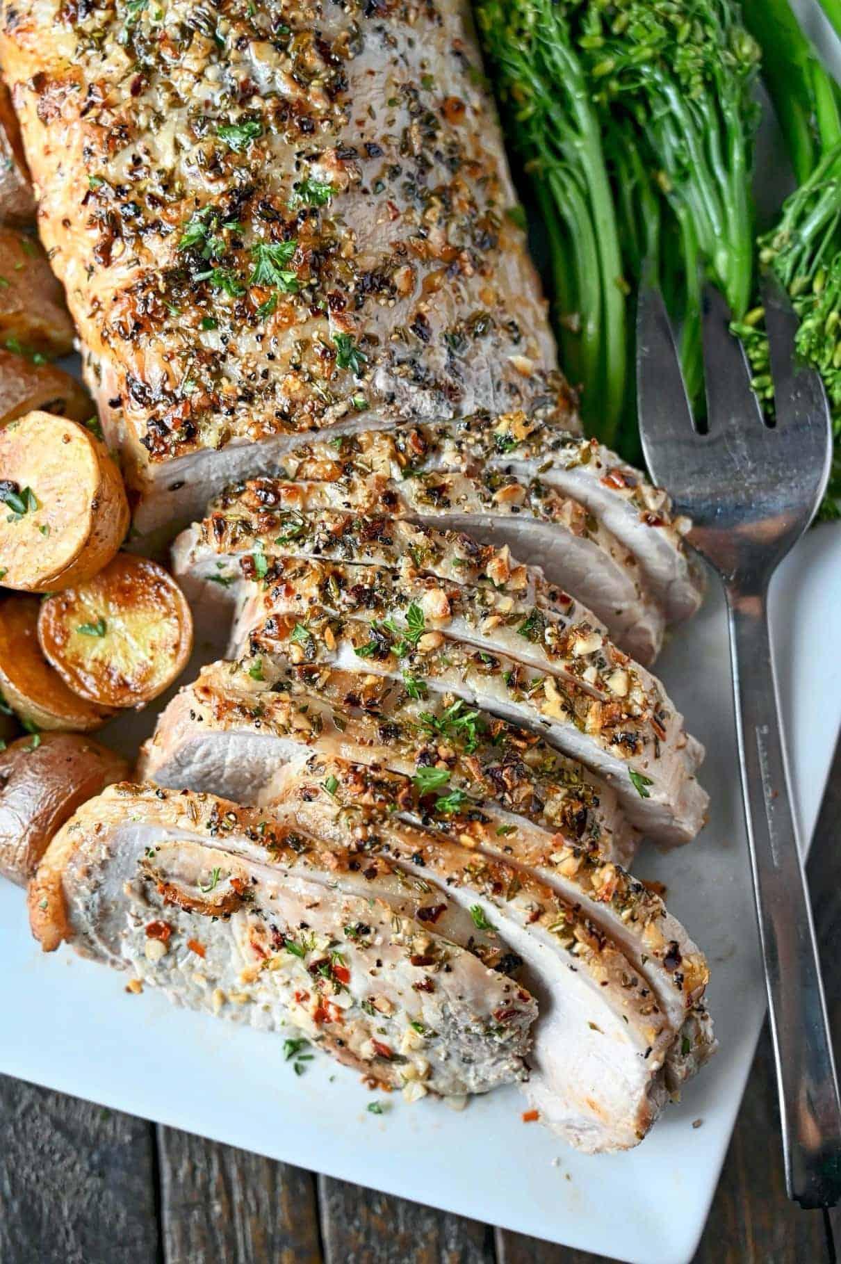 Filet de porc crustat cu ierburi feliat pe o farfurie albă.  Cu o latură de broccolini și cartofi prăjiți.