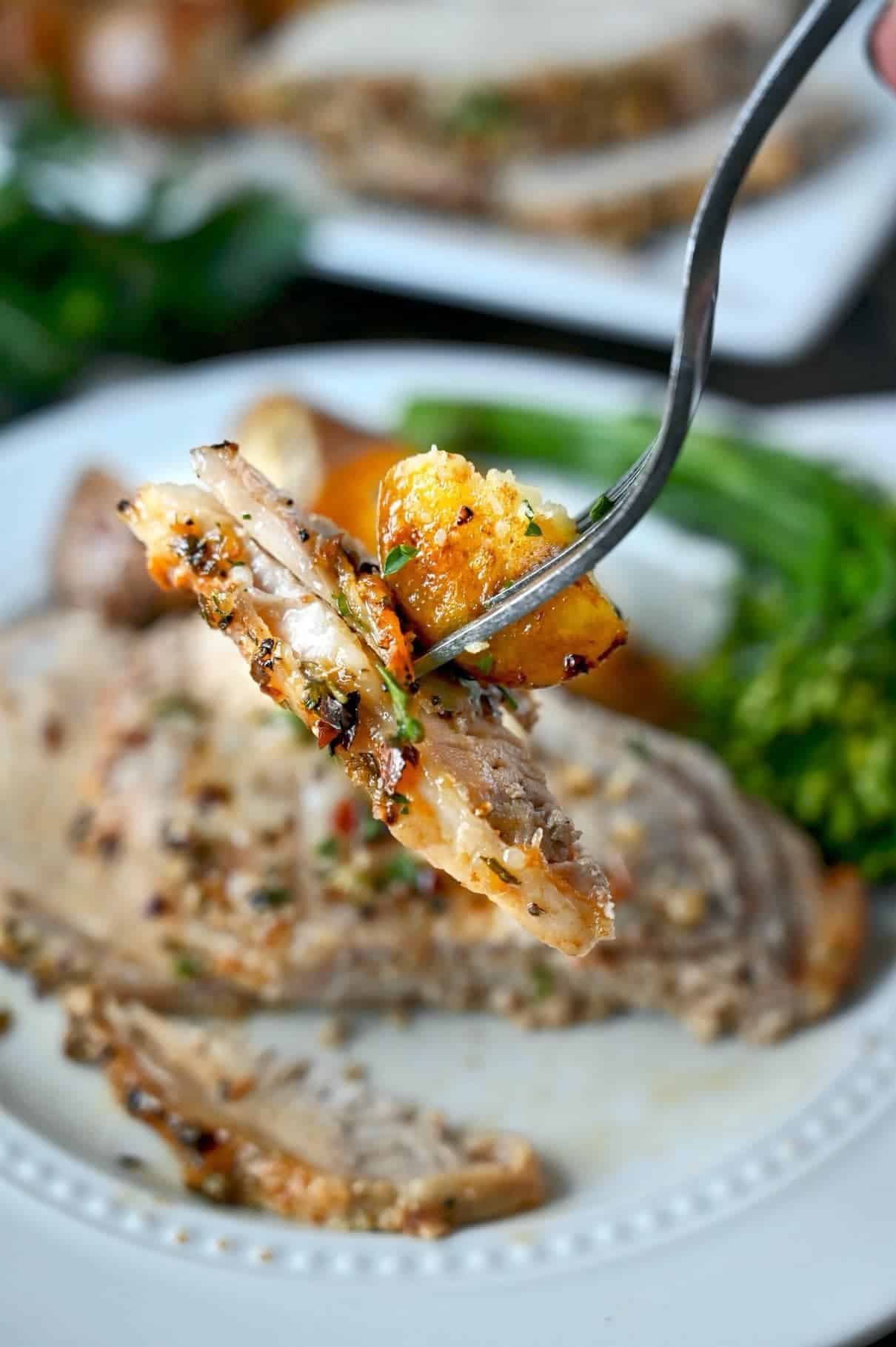 O furculiță care ridică o bucată de porc și cartofi.