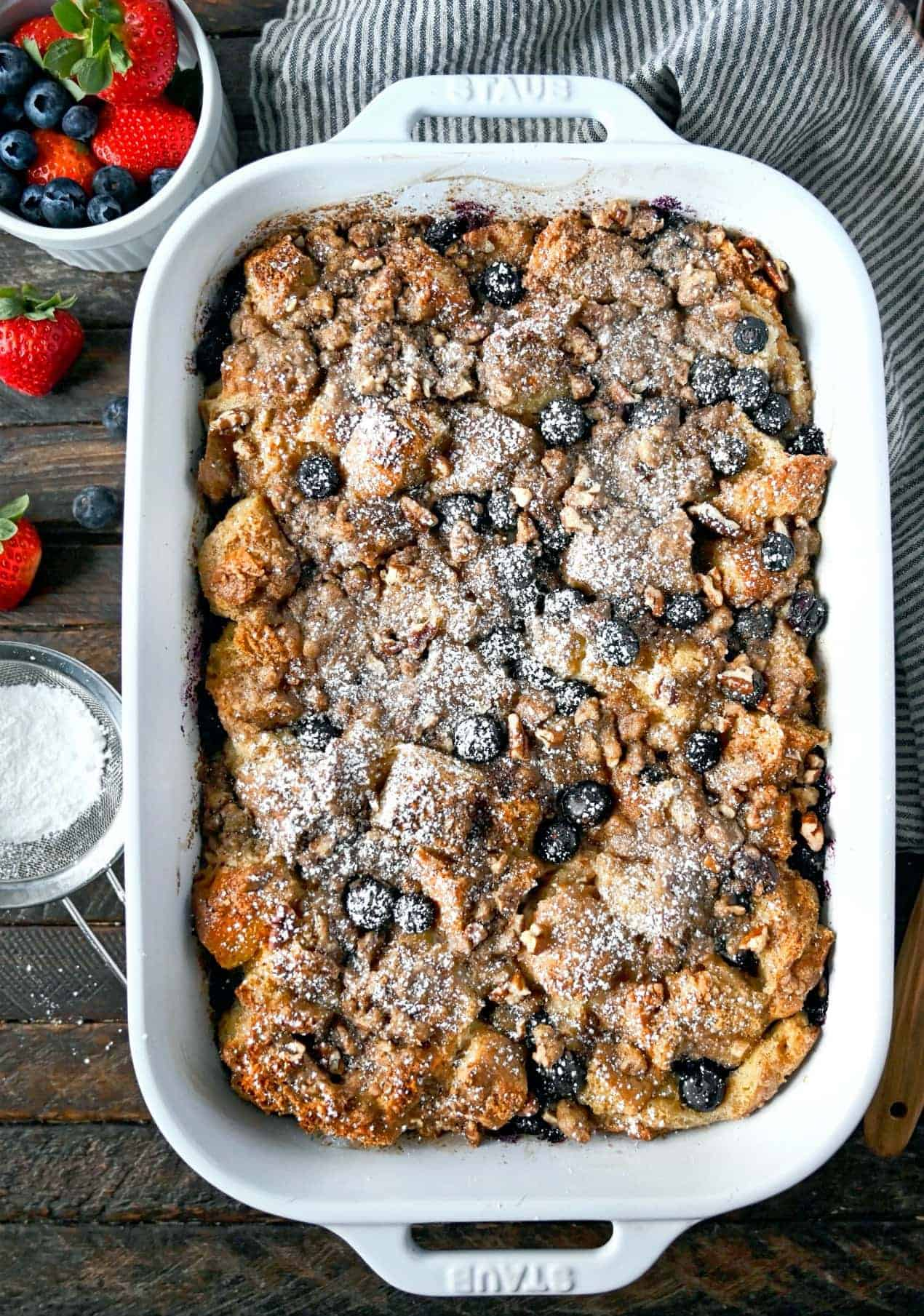 Blueberry french toast casserole in a white baking dish with powdered sugar sprinkled on top.