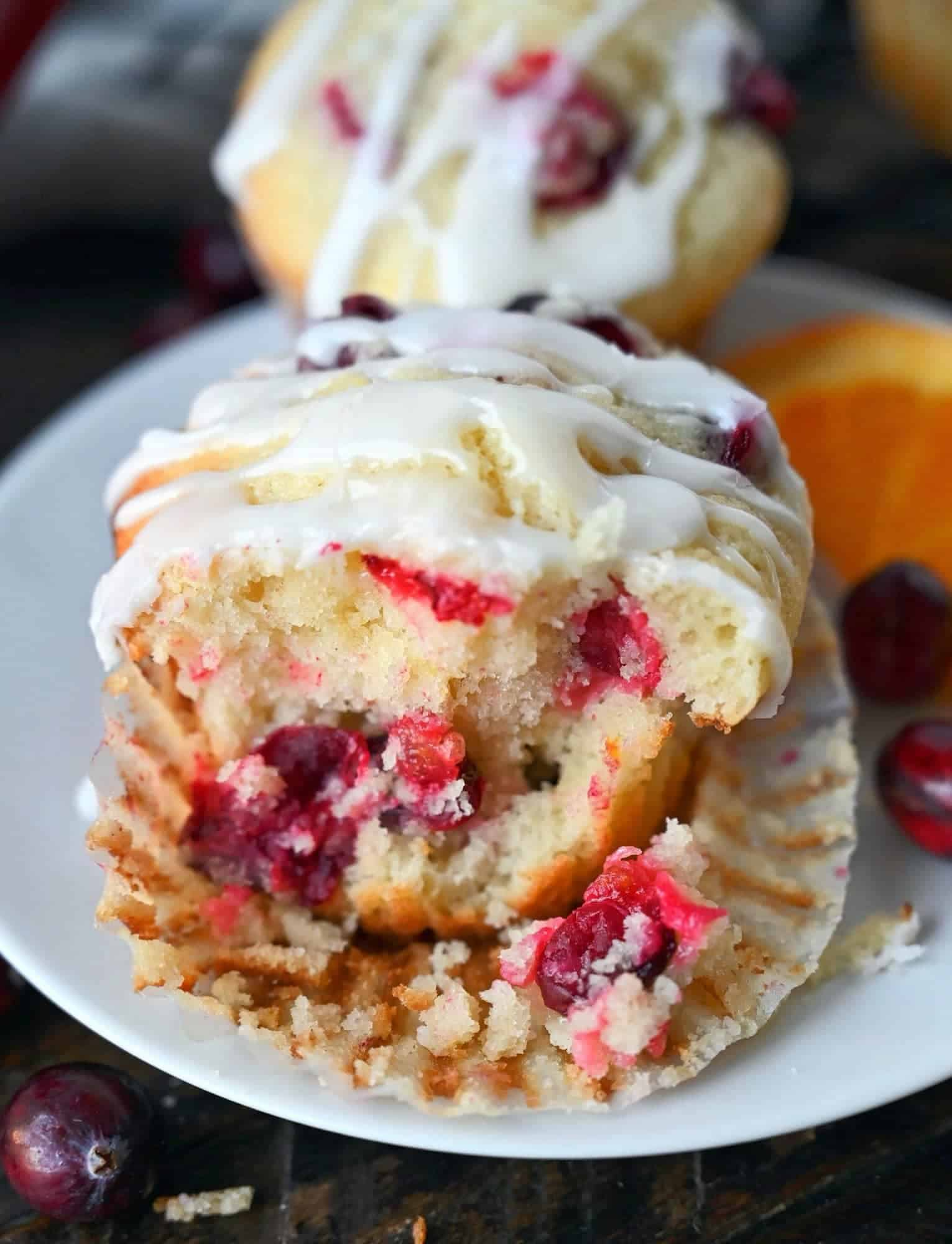 Cranberry orange muffin with a chunk removed from the front.