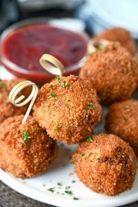 Deep fried stuffing balle with a dervinh toothpick in each one.