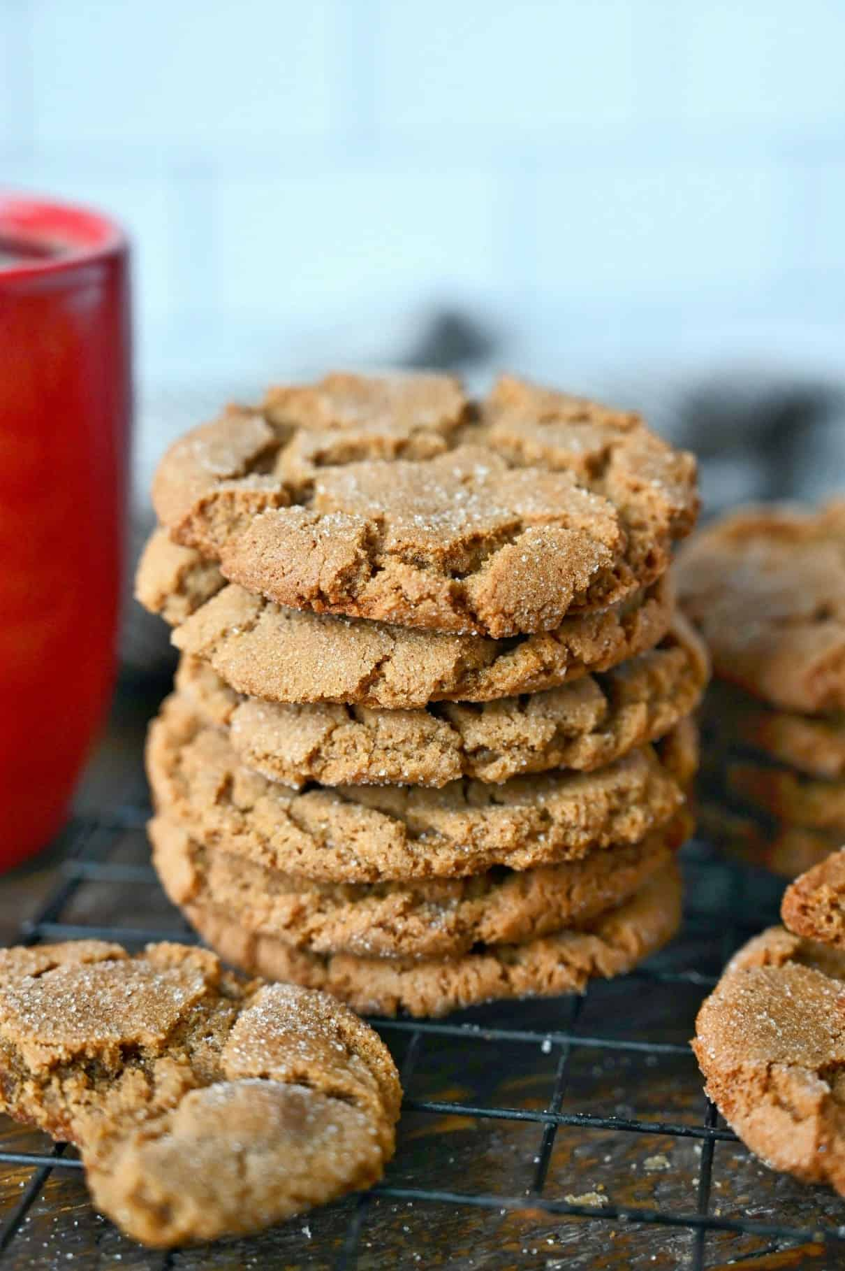 Ginger snap cookies stalked uo on a cooling rack.