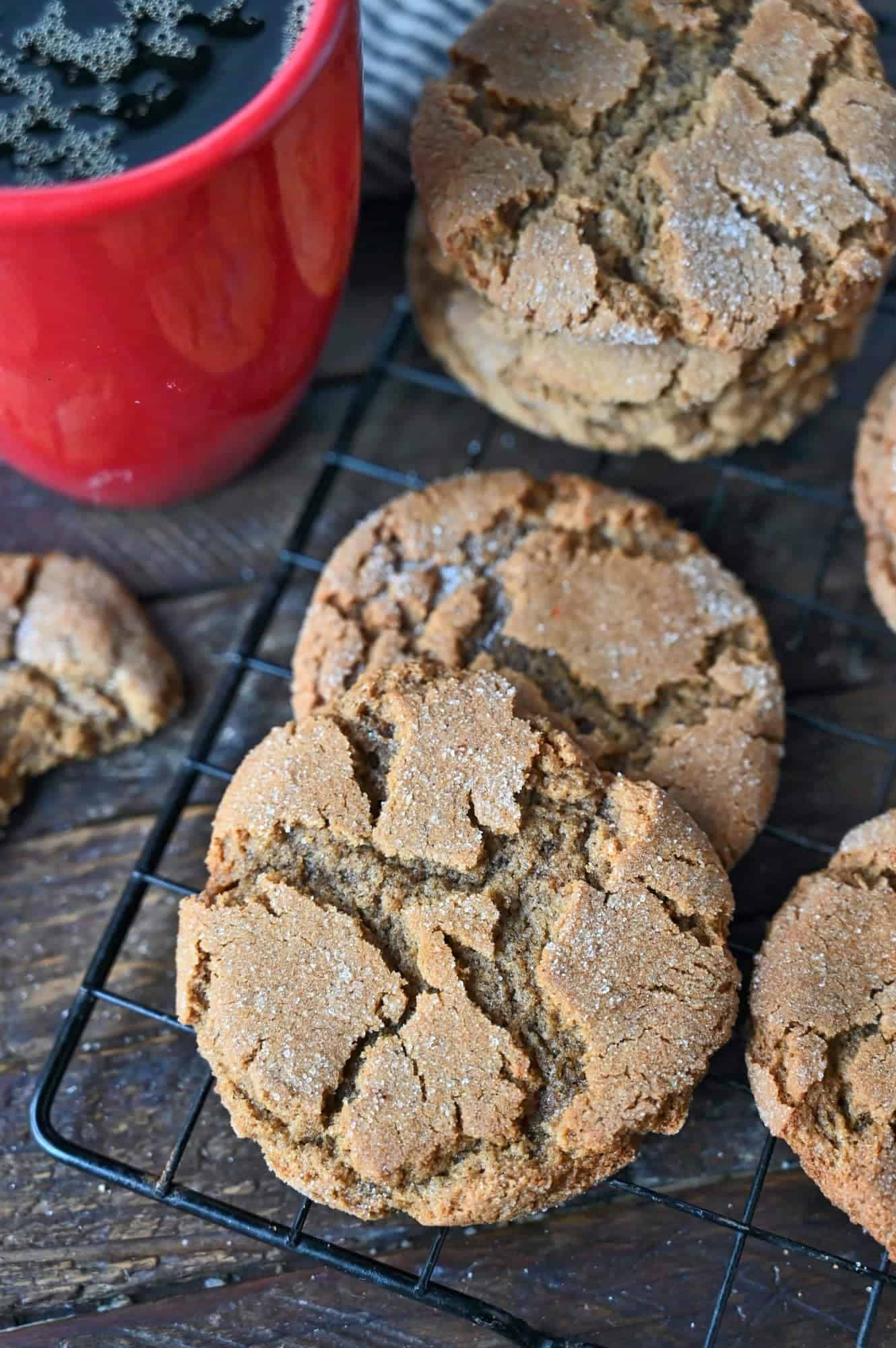 Ginger snap cookies on a cooling rack and a red coffee cup.