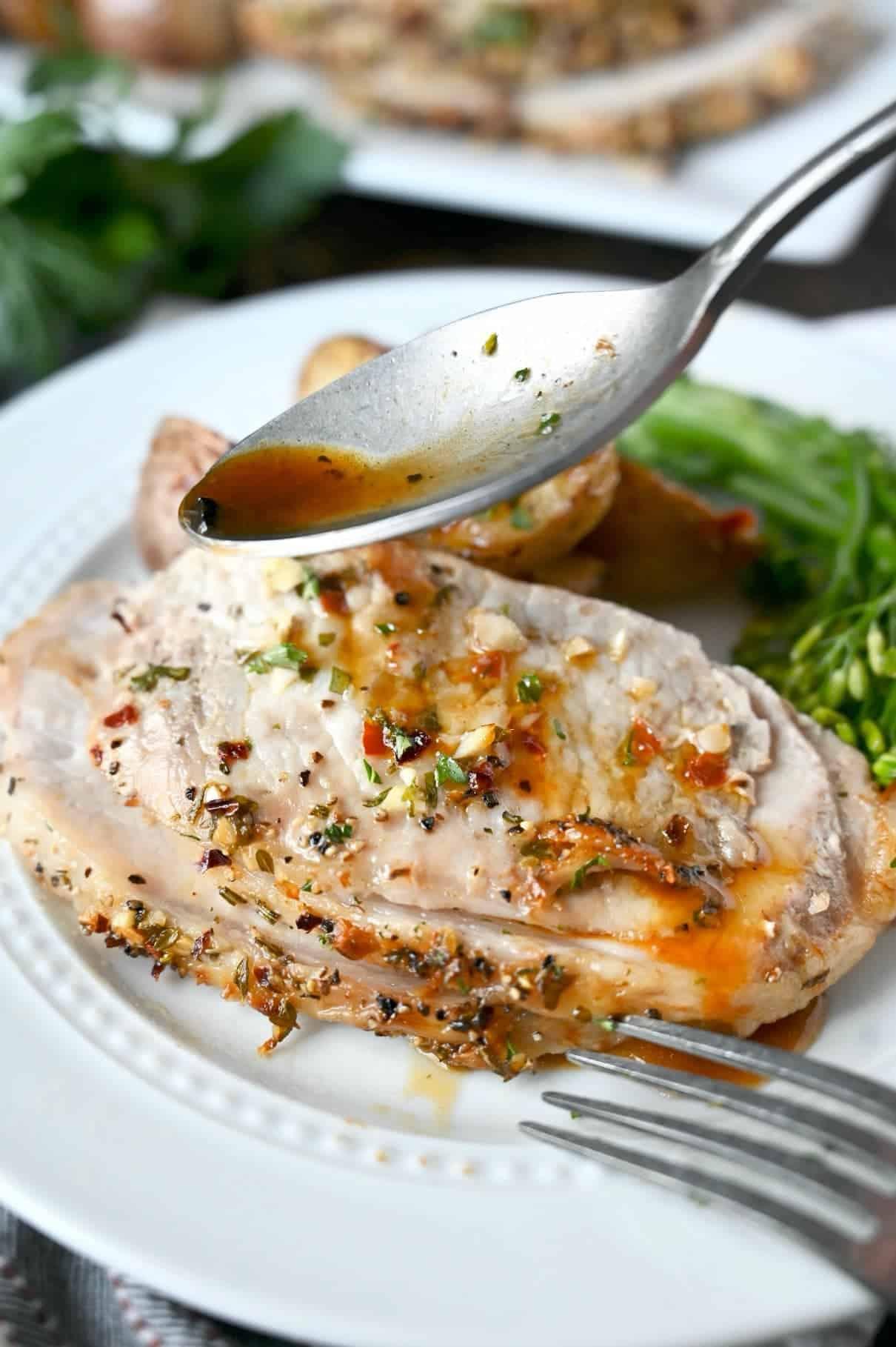 O felie de filet de porc într-o crustă de ierburi pe o farfurie albă cu broccoli și cartofi prăjiți.