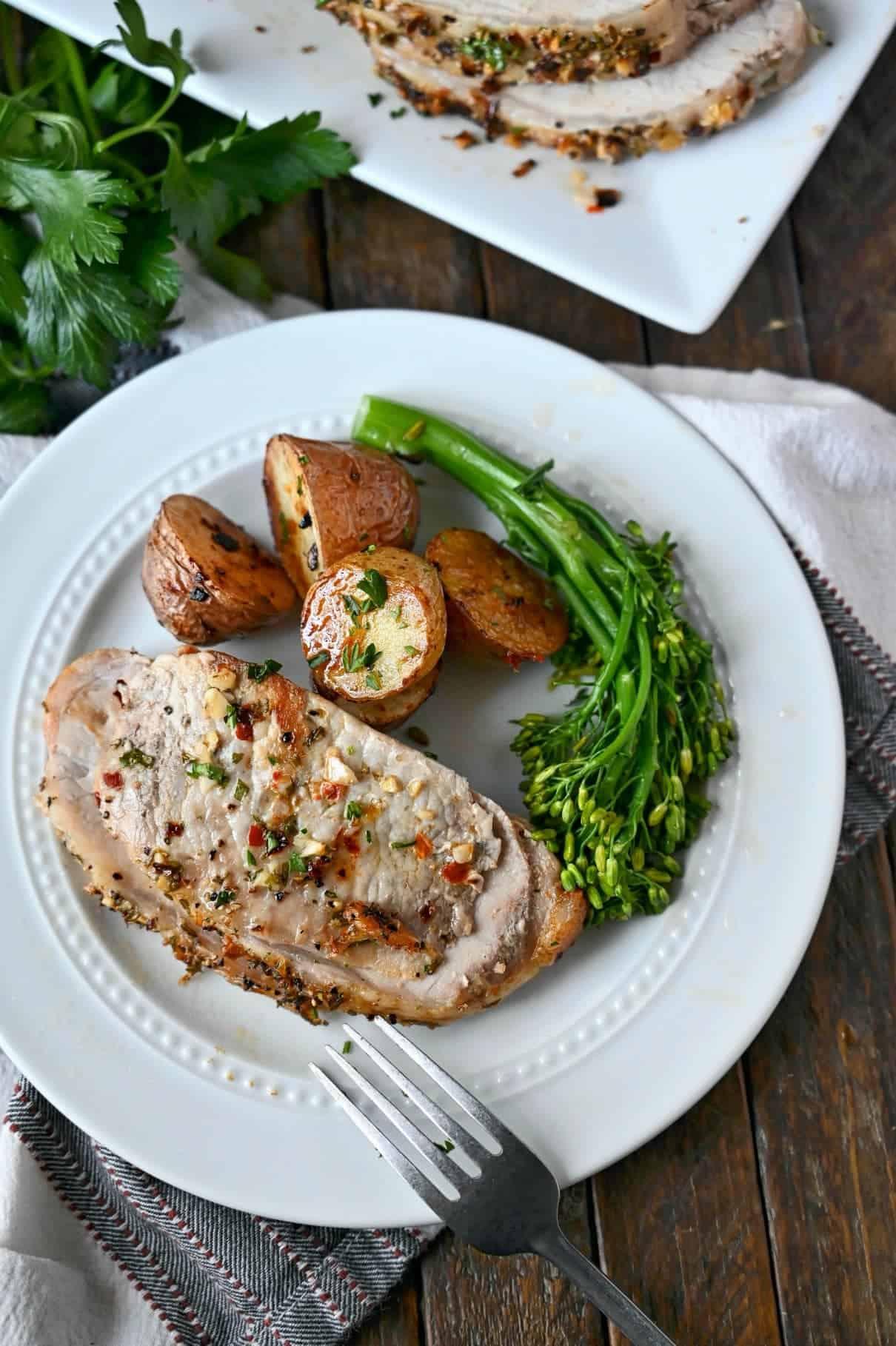 Felie de porumb de porc pe o farfurie albă, cu o parte de cartofi prăjiți și broccolini.