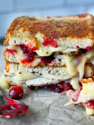 Two turkey cranberry brie sandwich on top of each other with a spoon full of cranberry sauce on the side.