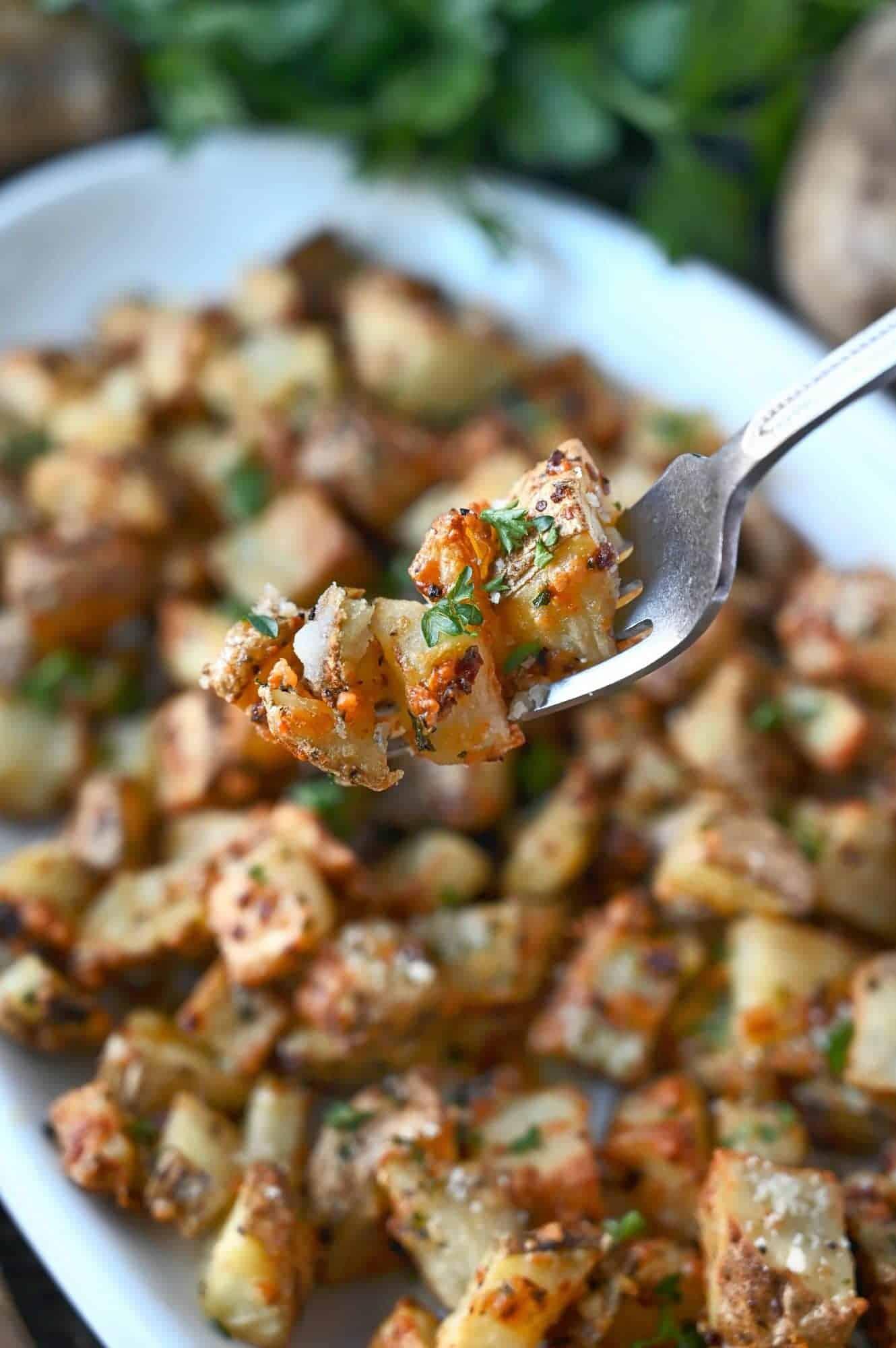 garlic parmesan potatoes on a fork.