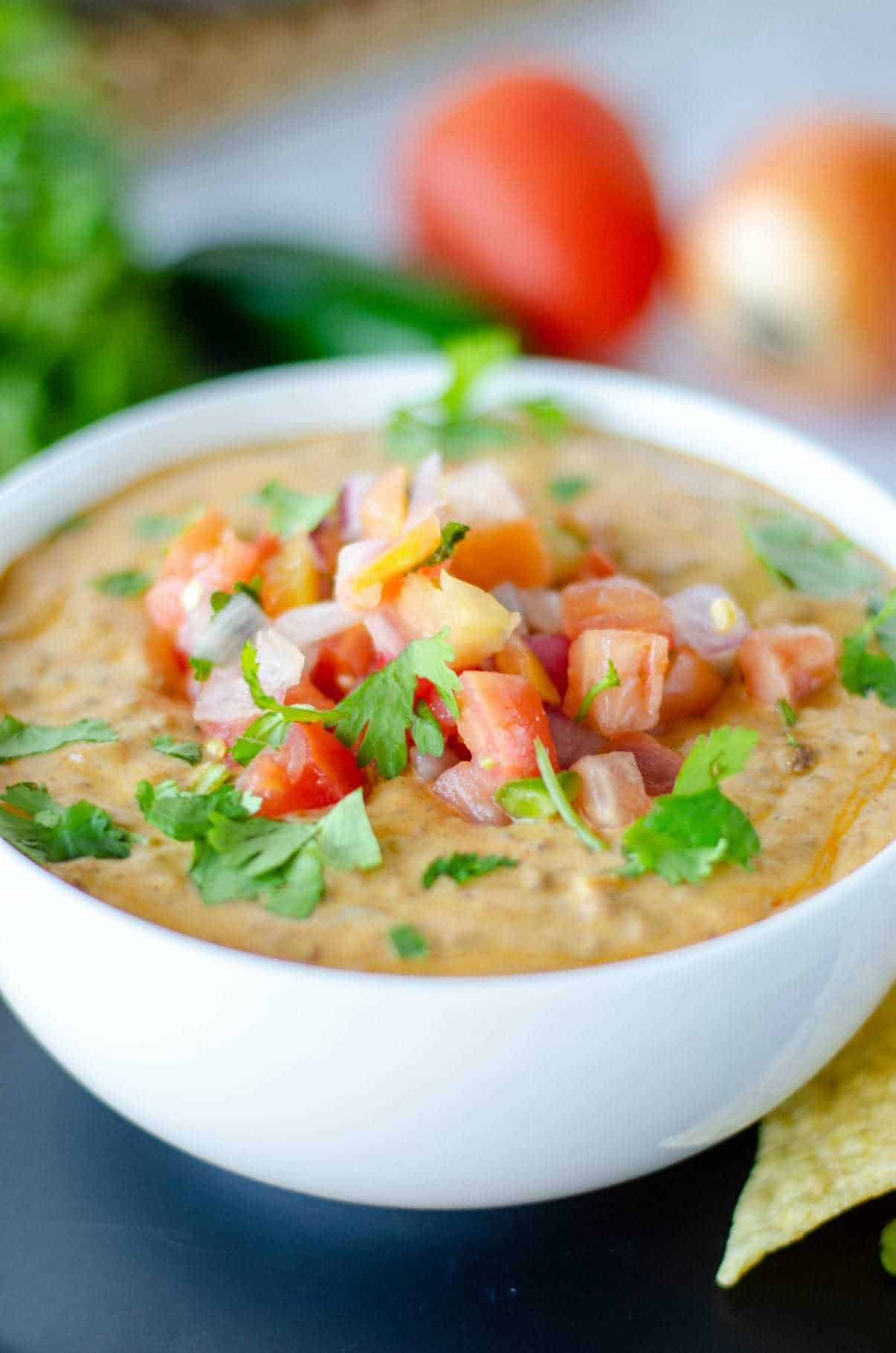 Chili con queso in a white bowl with diced tomatoes, onions and cilantro on top.