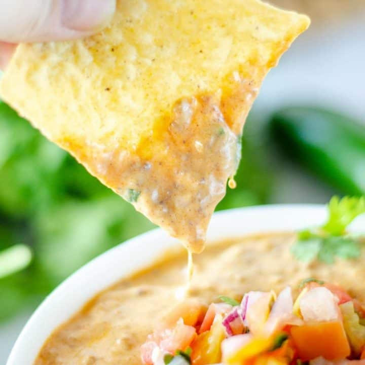 Chili con queso on a tortilla chip being dipped in.