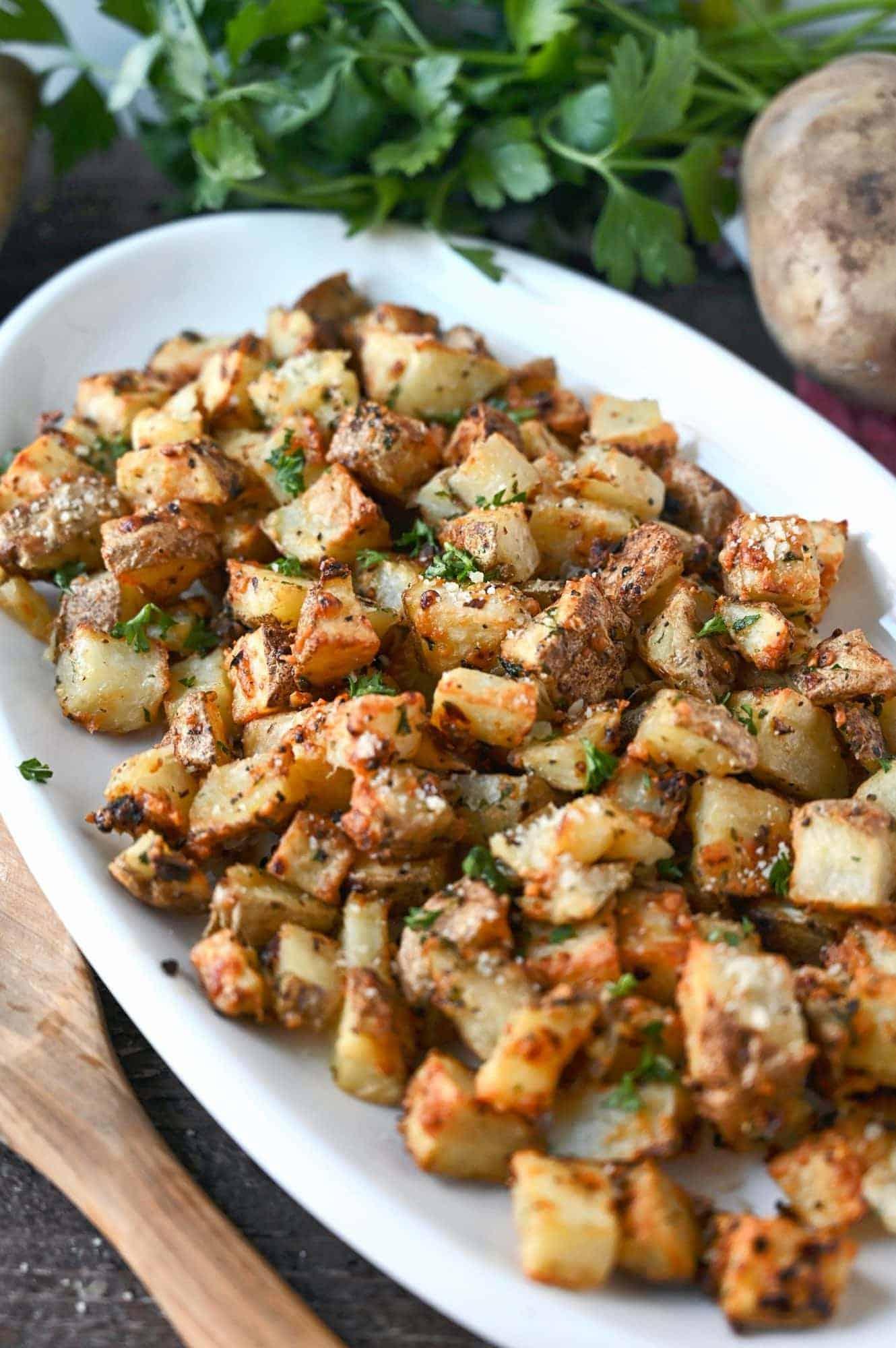 air fryer garlic parmesan potatoes on a white platter.